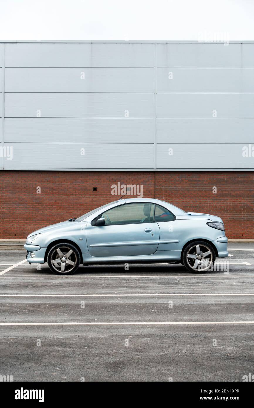 A Peugeot 206 CC compact coupe, parked in front of a grey prefabricated retail unit in Consett, County Durham, UK Stock Photo