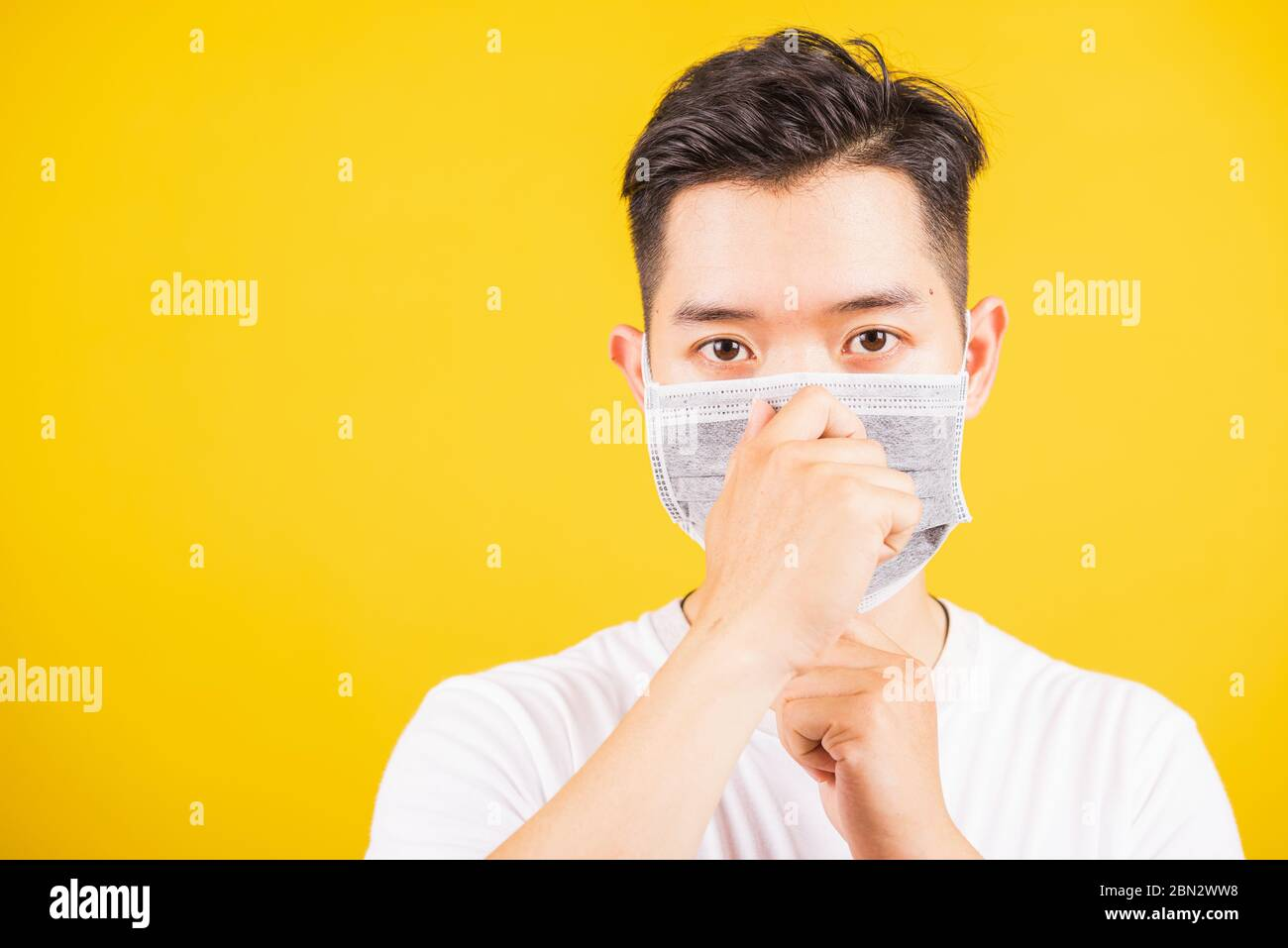 Portrait Asian handsome young man wearing face mask protective against coronavirus or COVID-19 virus showing demonstrating correct step, studio shot i Stock Photo