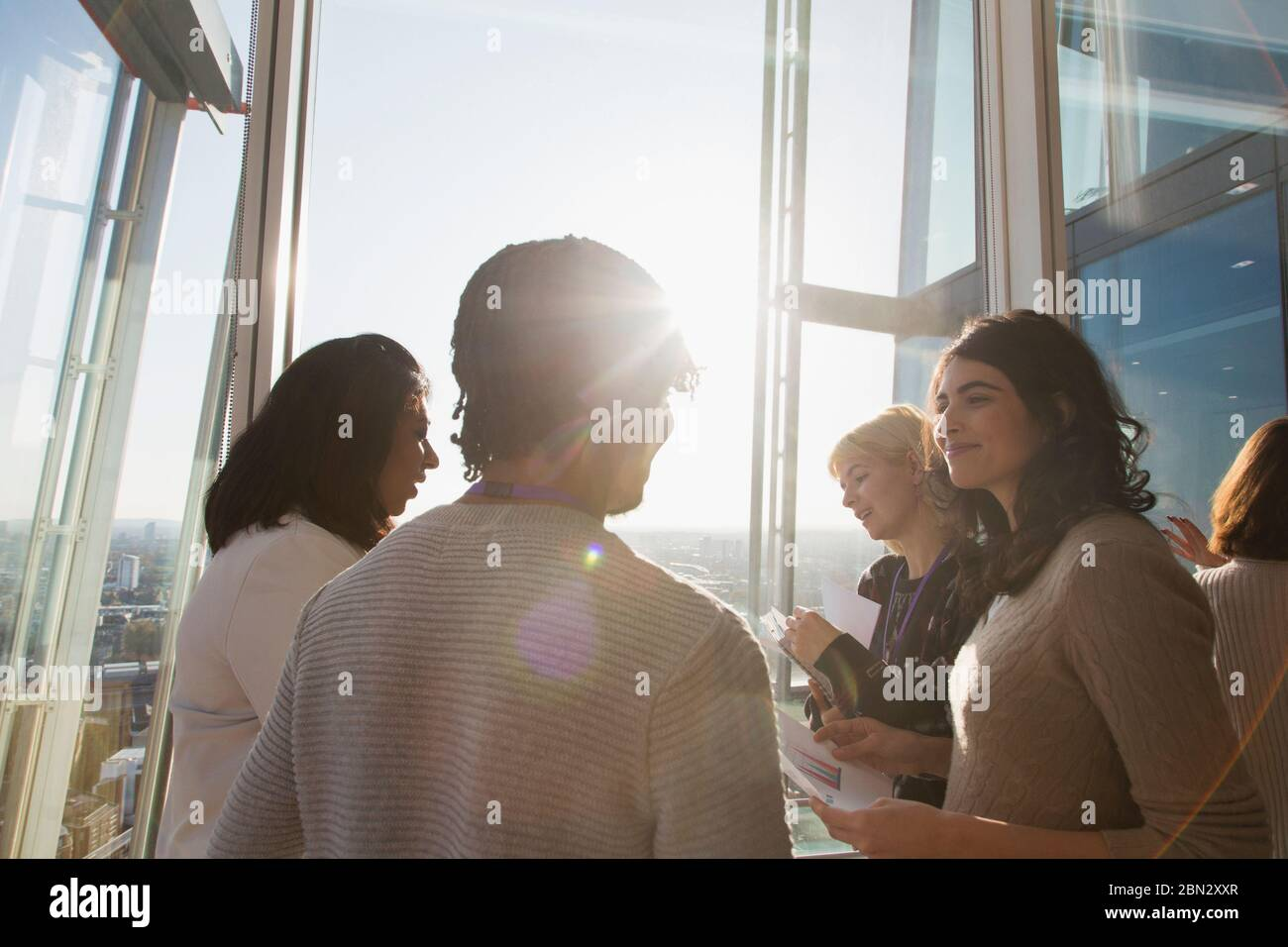 Business people talking at sunny office window Stock Photo