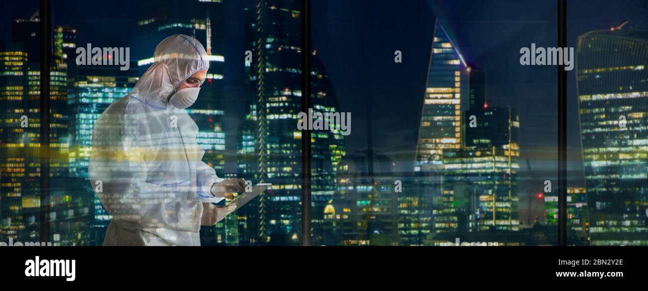 Male scientist in clean suit working late in city window Stock Photo