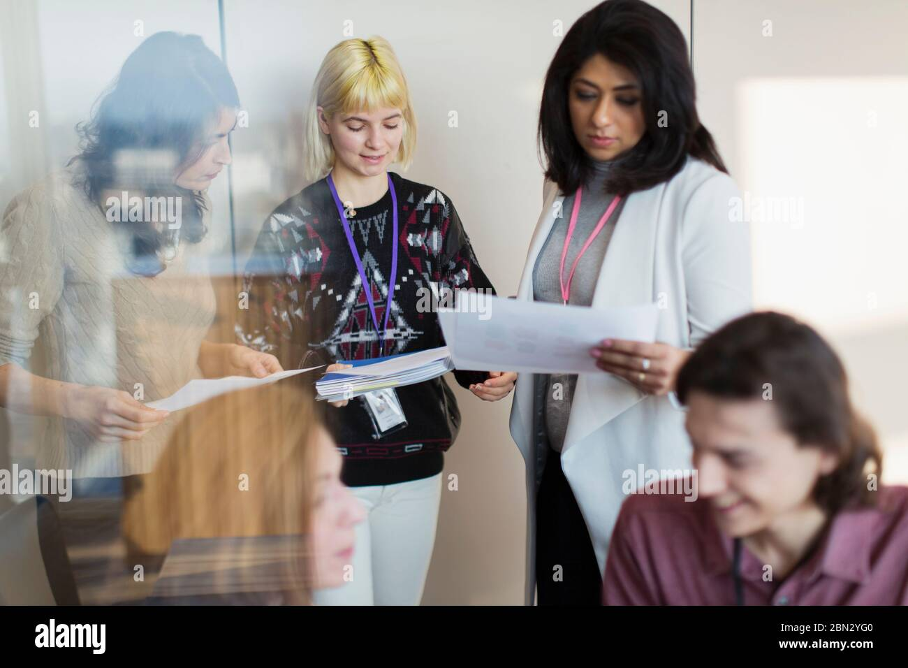 Businesswomen reading and discussing paperwork in meeting Stock Photo