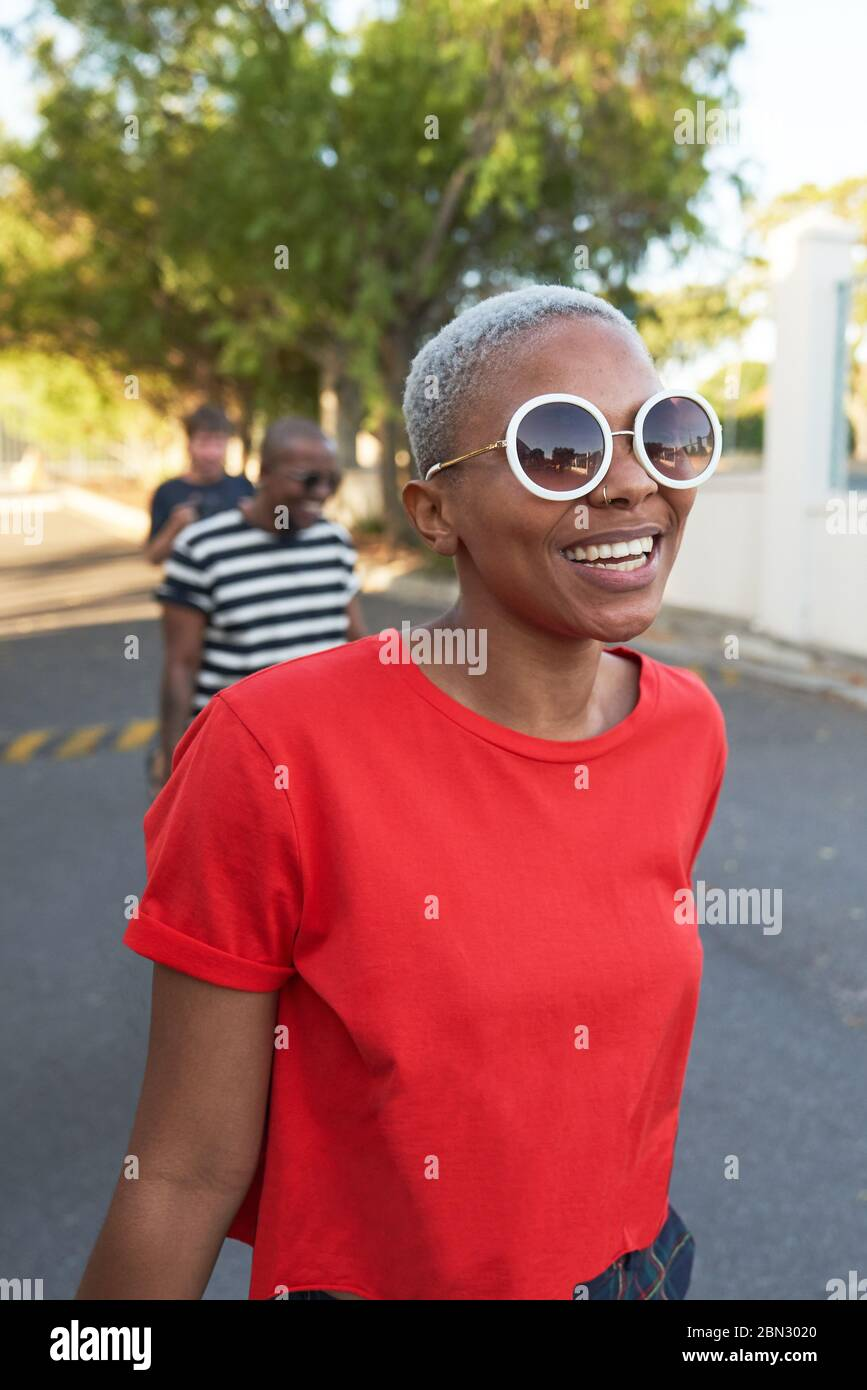 Happy young woman in sunglasses walking in street Stock Photo