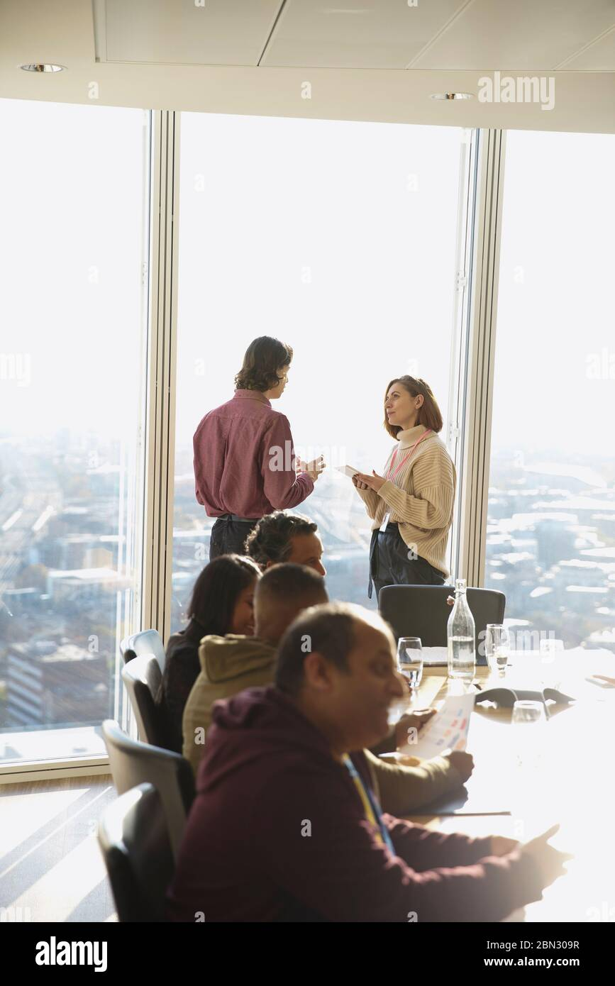 Business people talking at sunny highrise office window Stock Photo