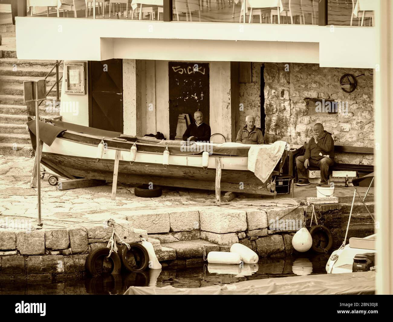 Mediterranean senior male people sitting seated chatting near wooden boat retro look sepia monochrome almost Black and White Lovran Croatia Europe Stock Photo
