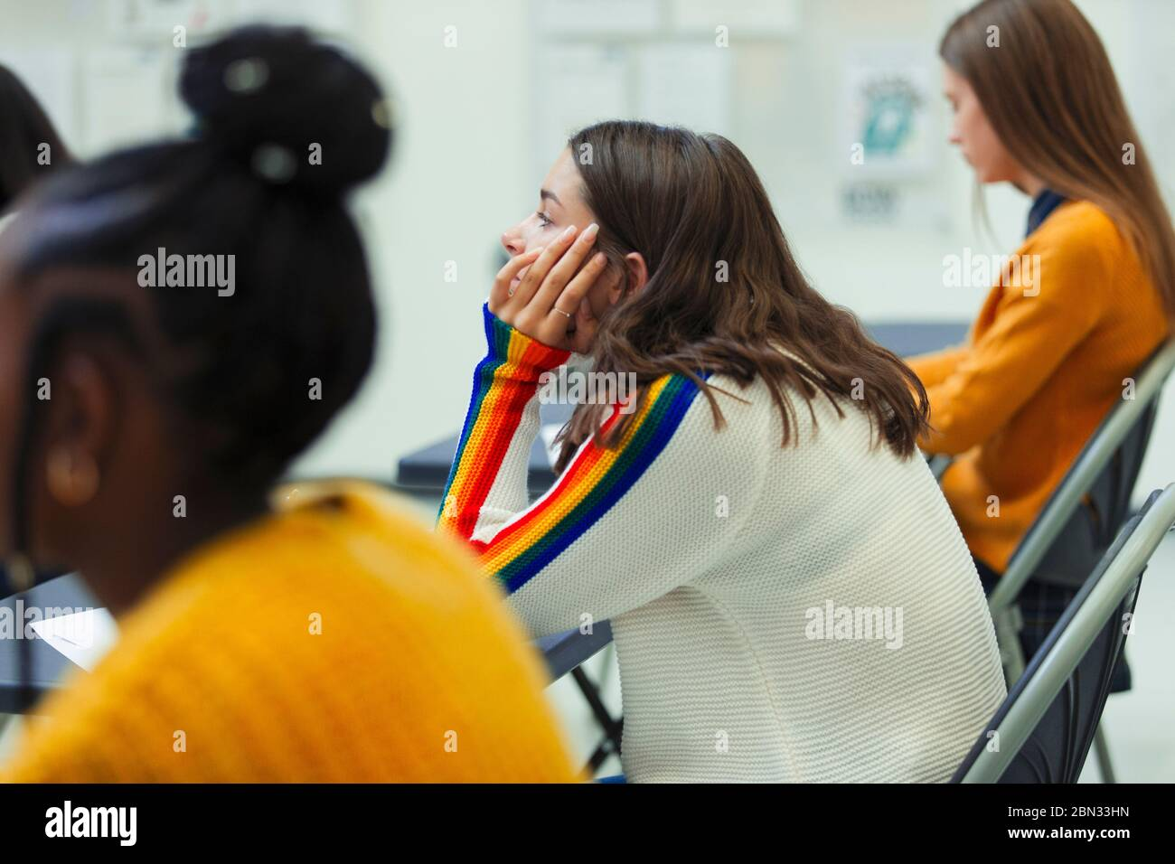 High school girl student taking exam at desk in classroom Stock Photo