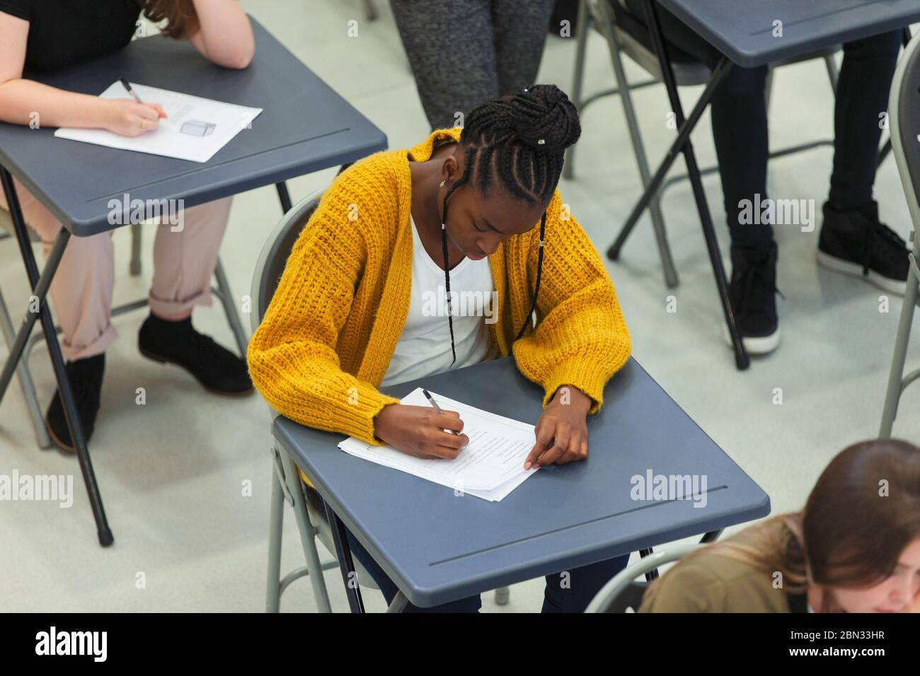 Focused high school girl student taking exam at desk in classroom Stock Photo