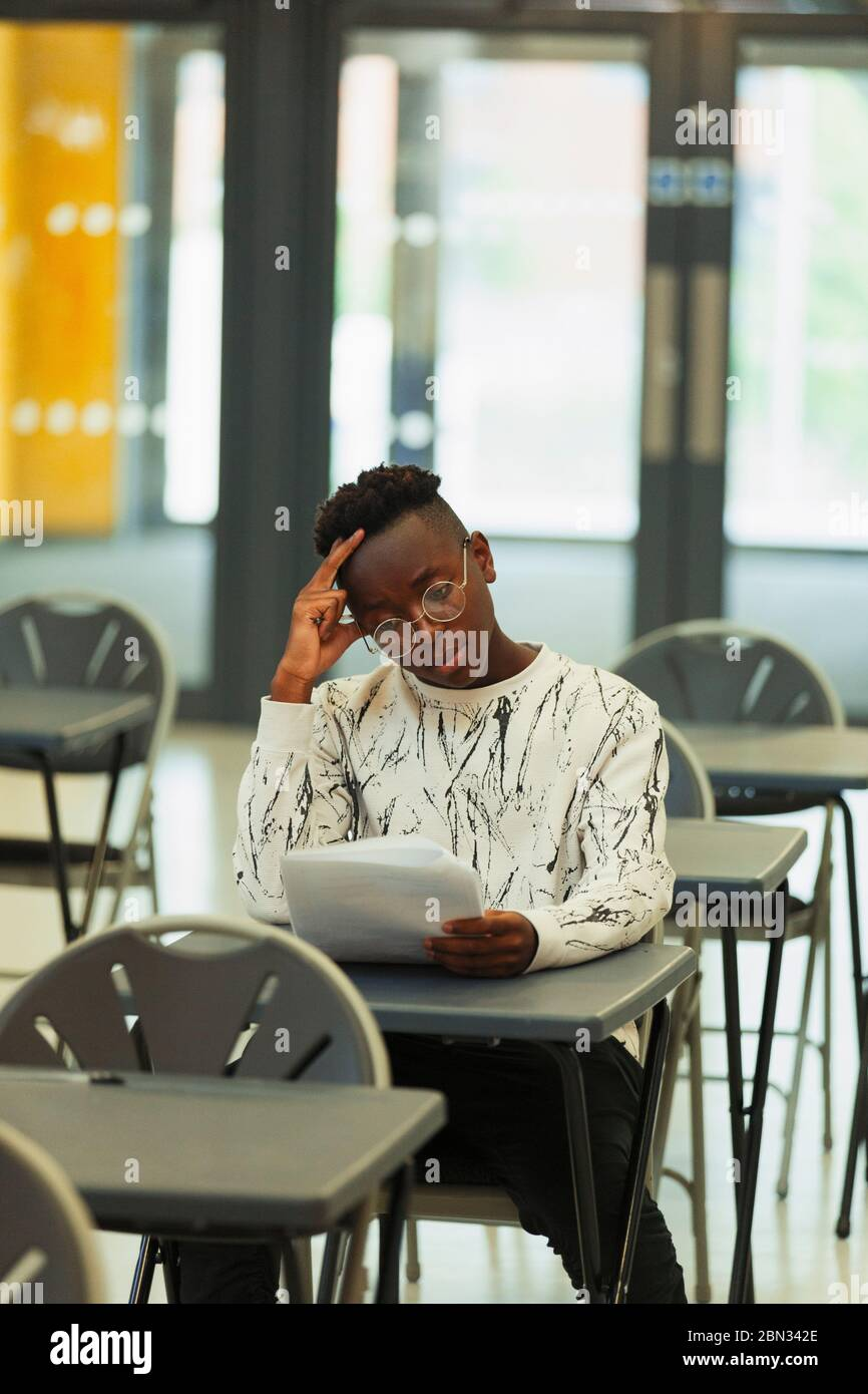 Focused high school boy student taking exam at desk in classroom Stock Photo