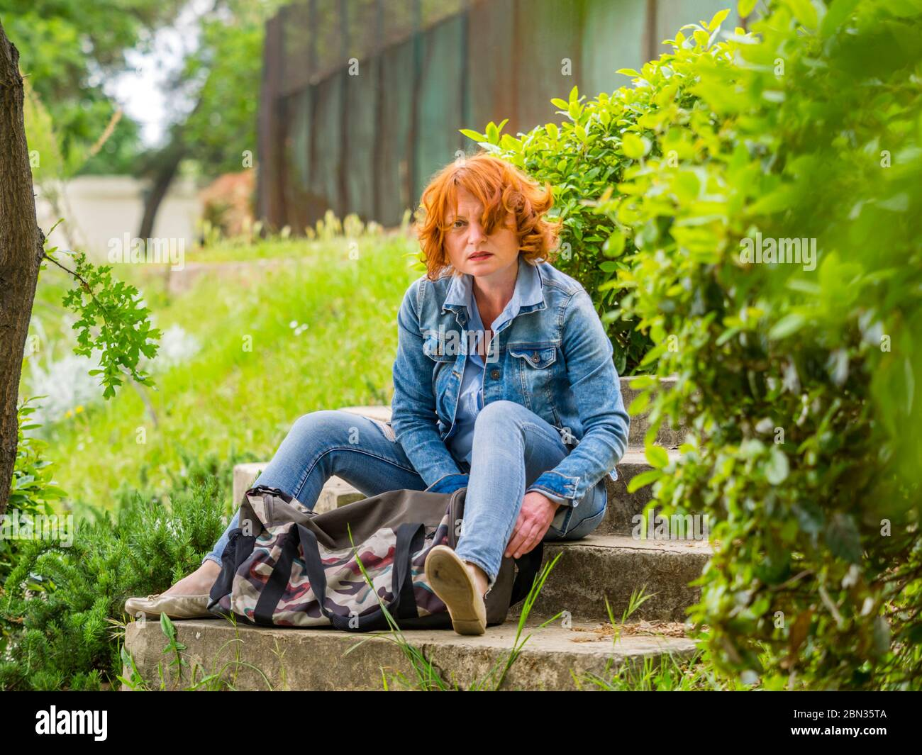 Good-looking ginger hair curly curls redhaired redhair midadult woman outdoors seated with handbag bag in front resting serious eyeshot Stock Photo