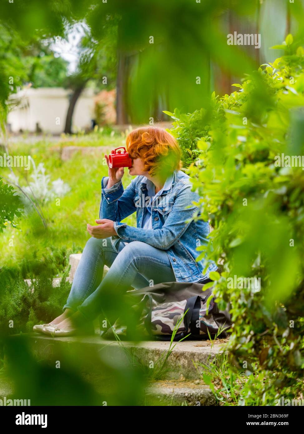 Good-looking ginger hair curly curls redhaired redhair midadult woman outdoors seated with handbag bag and drinking coffee from Red cup refreshment Stock Photo