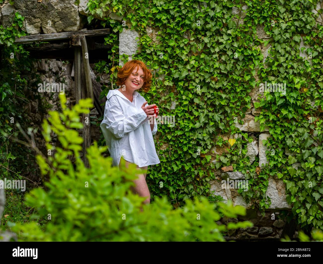 Good-looking ginger hair curly curls redhaired redhair midadult woman outdoors in remote abandoned place house hand hands hold holding Red coffee cup Stock Photo