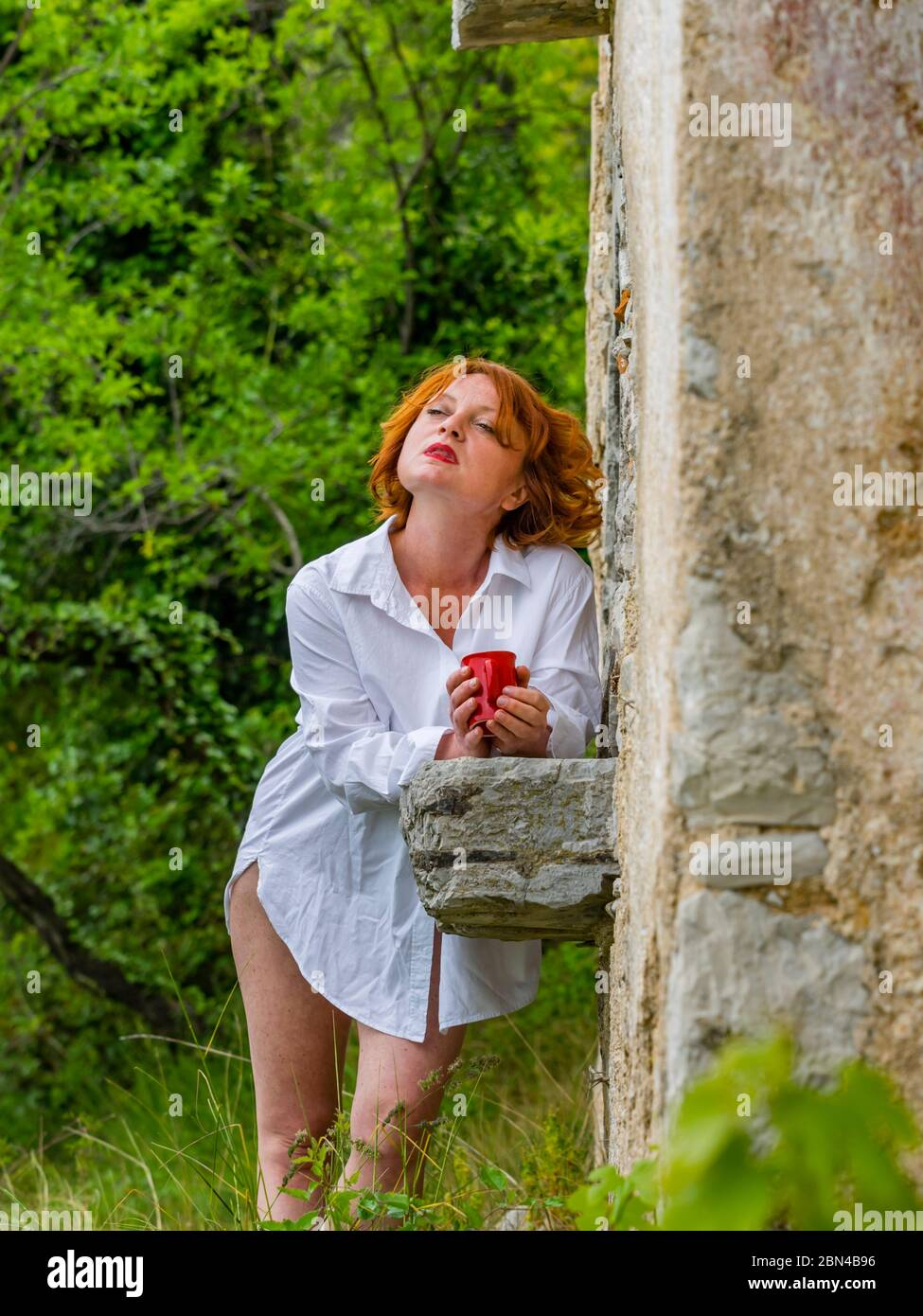 Ginger hair curly curls redhaired redhair midadult woman outdoors in remote abandoned place holding hand hands coffee Red cup looking away serious Stock Photo