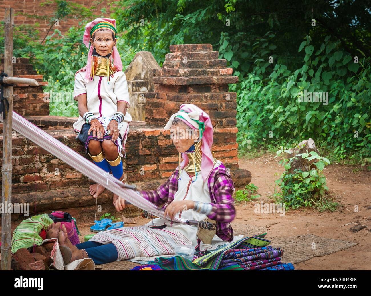 Bagan Myanmar - October 29 2013; Two Kayan women with brass rings around necks one weaving while other in selective focus sitting wall looks on. Stock Photo