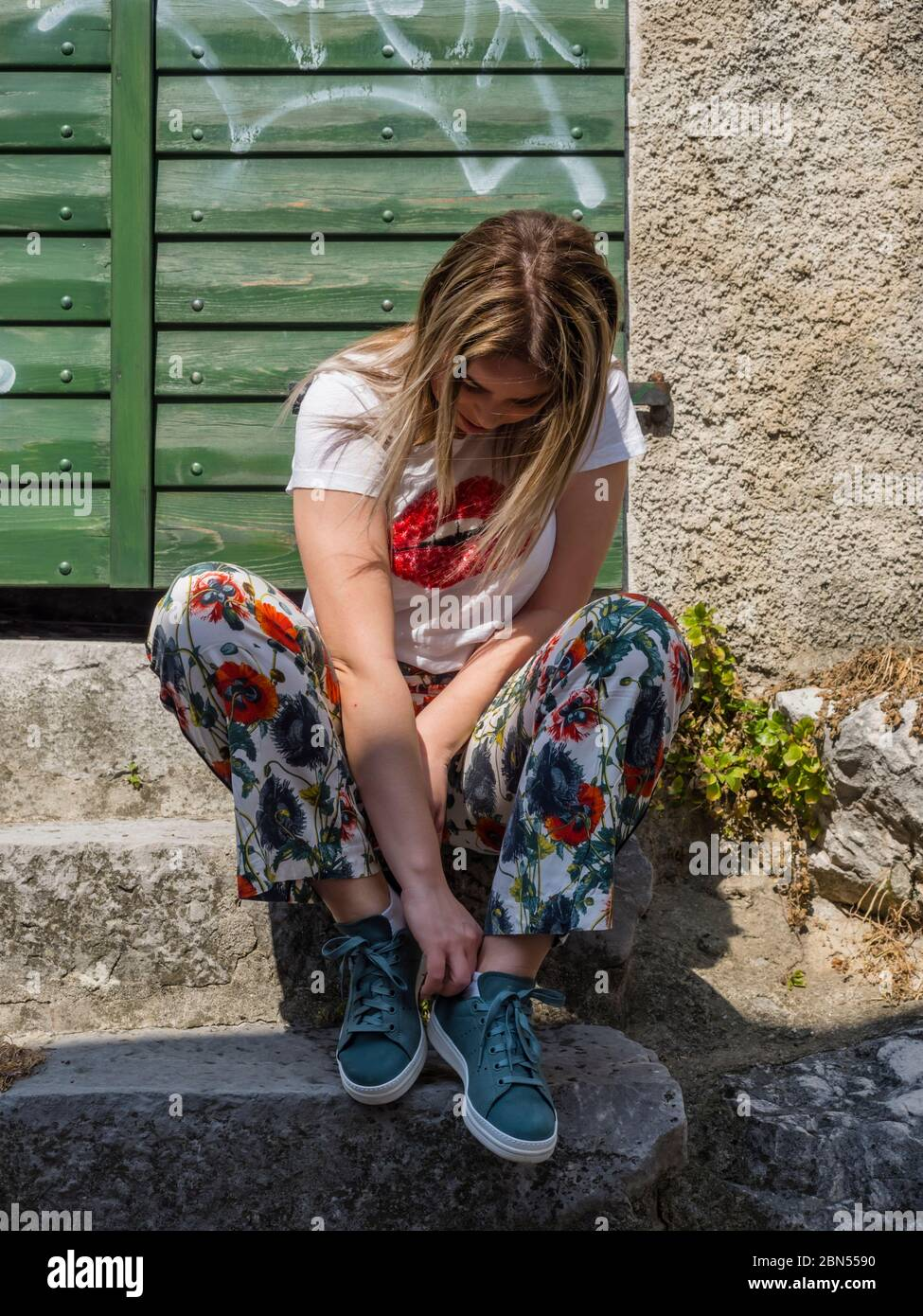 Teengirl tying sneakers Stock Photo