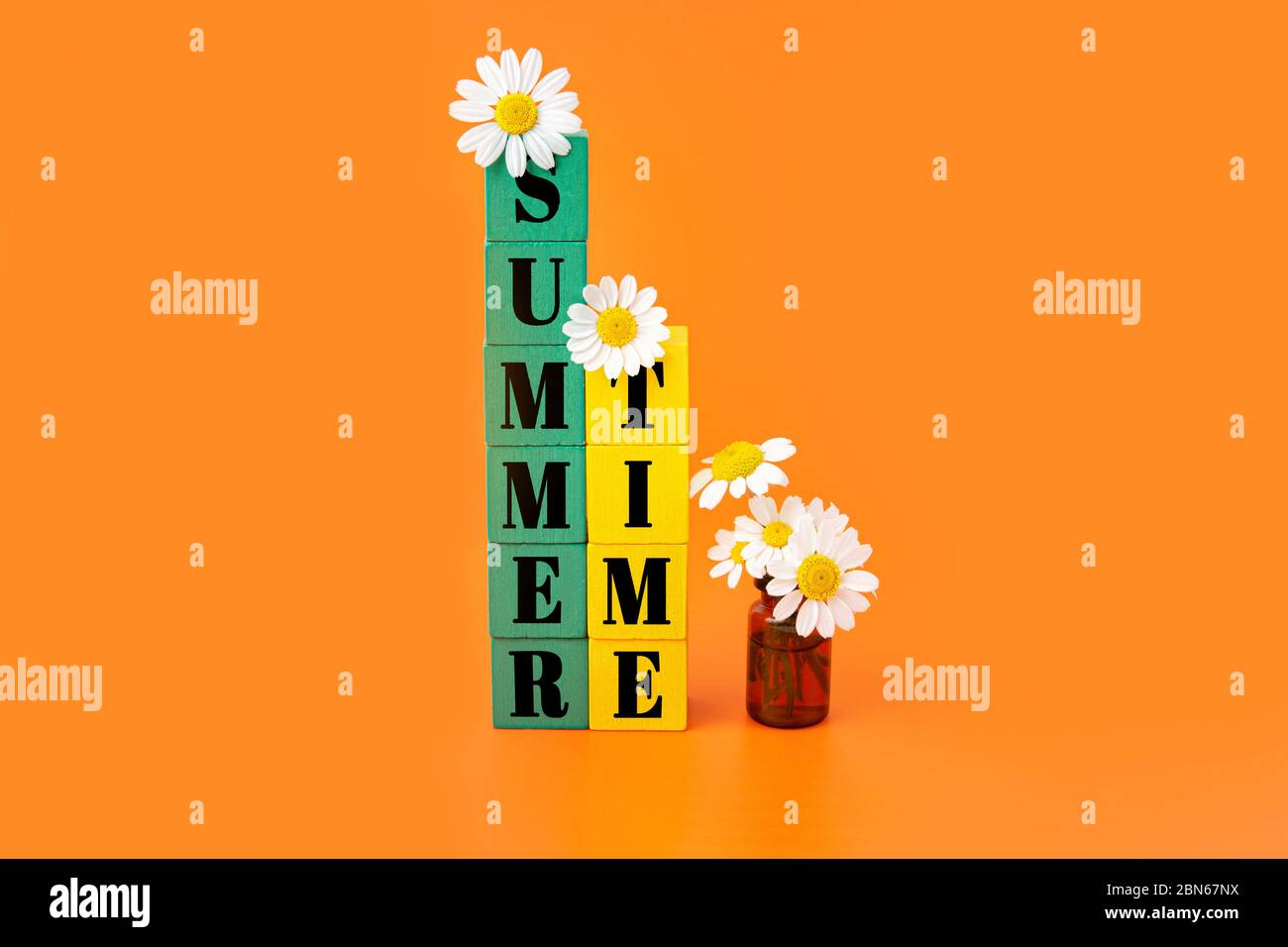 Summer time lettering written on two stacks of green and yellow wooden blocks decorated with chamomile flowers and a small glass bottle with blooming Stock Photo