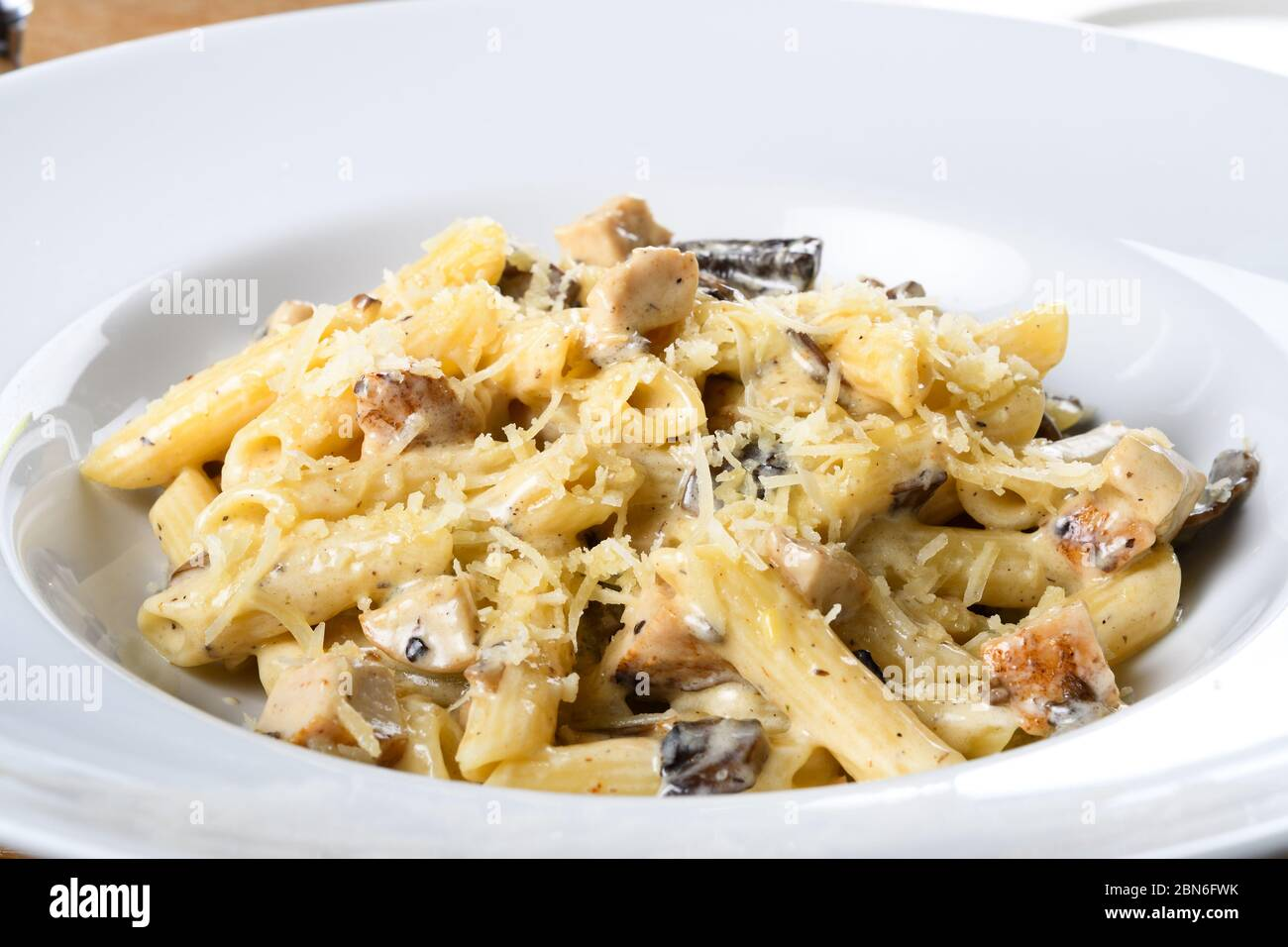 Traditional authentic italian penne al pollo e funghi pasta with mushroom ,chicken and parmesan cheese. Stock Photo