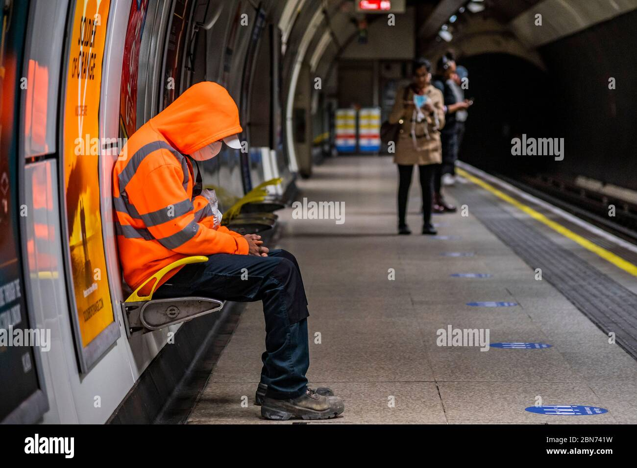 A worker in hi vis orange sits next to an advert for soldier of orange - behind him a womman removes her mask. Passenger numbers remain dramatically down on the tube, even during rush hour and even on teh first day of the easing of government guidance. Those who do travel attempt to obey the guidance on 2m social distancing and possibly around half wear masks - despite isntructions from teh Mayor of London that he expects everyone to wear a mask on public transport. The 'lockdown' continues for the Coronavirus (Covid 19) outbreak in London. Stock Photo