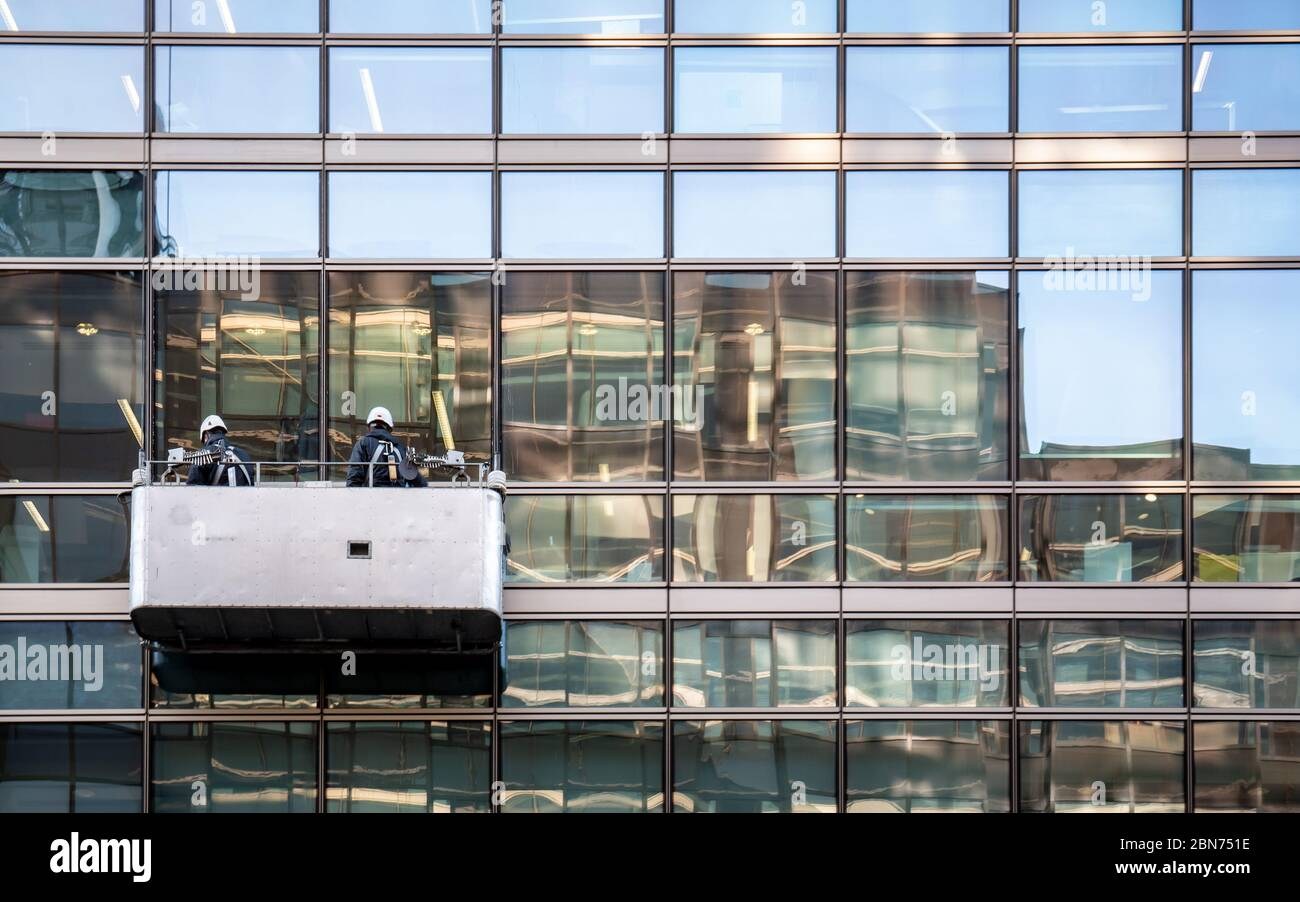 Window cleaners making use of a suspended cradle to clean the exterior of a contemporary glass and steel office block. Stock Photo