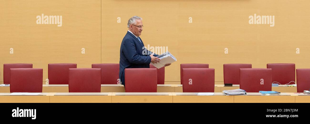 Munich, Germany. 13th May, 2020. Joachim Herrmann (CSU), Minister of the Interior of Bavaria, walks past the chairs during the session of the Bavarian parliament through the empty government bench. Topics of the session on 13.05.2020 include a change in the law on the use of health resort contributions for public transport and the current border controls in the wake of the Corona pandemic. Credit: Peter Kneffel/dpa/Alamy Live News Stock Photo