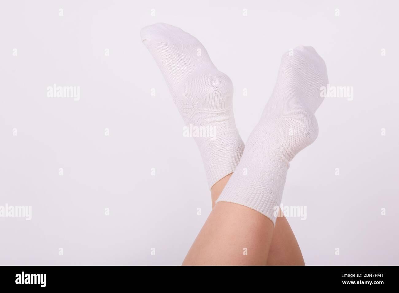Female legs in white cotton socks on white background. Ladies wearing sports socks Stock Photo