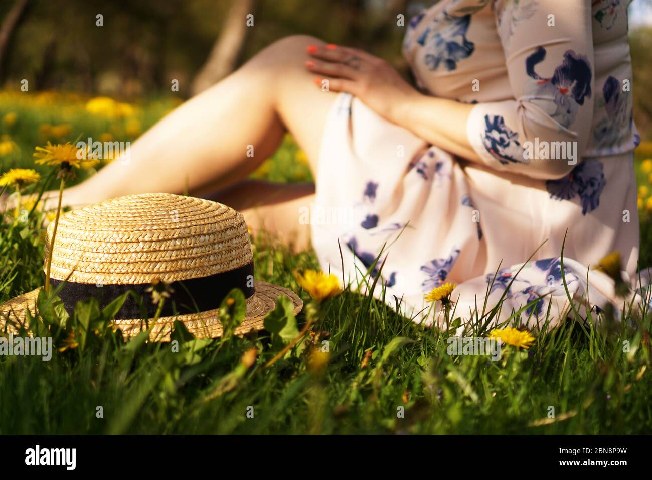 Woman with a straw hat in a flower field and green grass. Summer in the country. Focus on hat Stock Photo