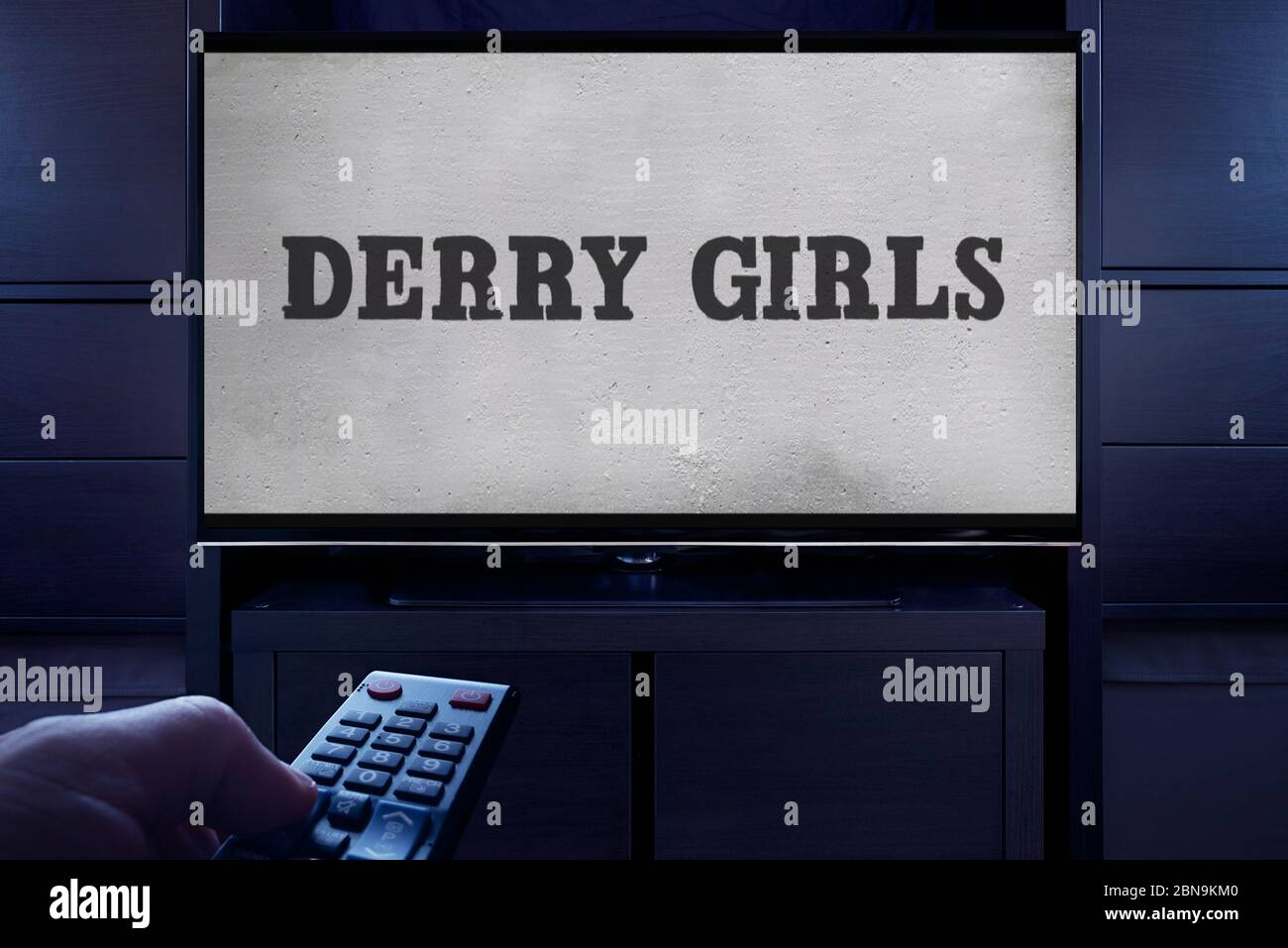 A man points a TV remote at the television which displays the Derry Girls main title screen (Editorial use only). Stock Photo
