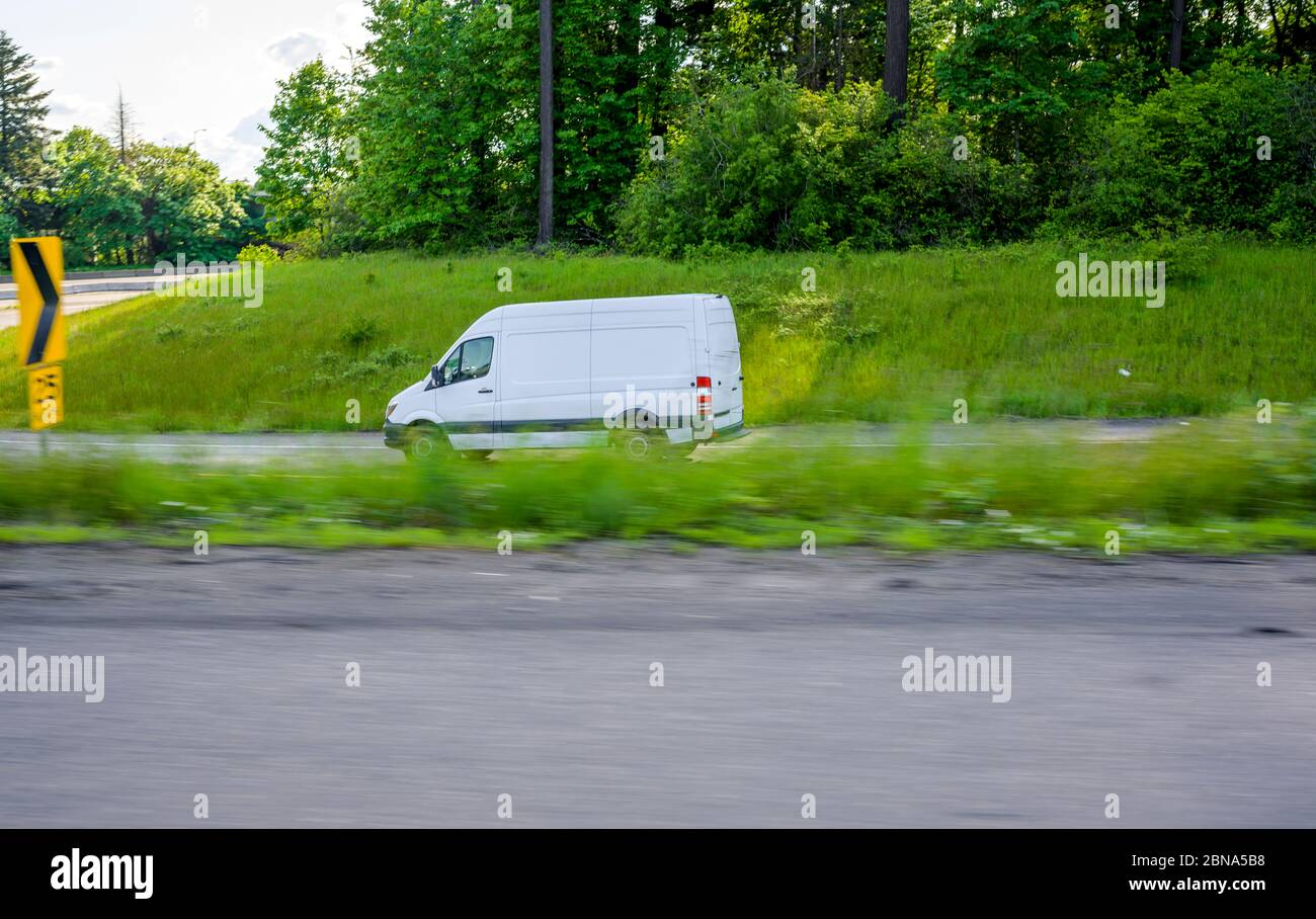 Commercial efficient eco-friendly transportation compact mini van for small business and local deliveries running on the highway entrance with green g Stock Photo