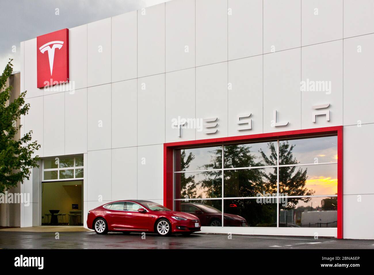 Exterior of Tesla Tysons Corner-Tyco Road store, Vienna, Virginia, USA, with red Model S electric car in front of window reflecting sunset post-storm Stock Photo