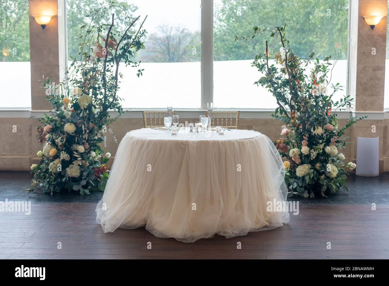 A small white table for two personas and beautiful floral wedding decorations Stock Photo