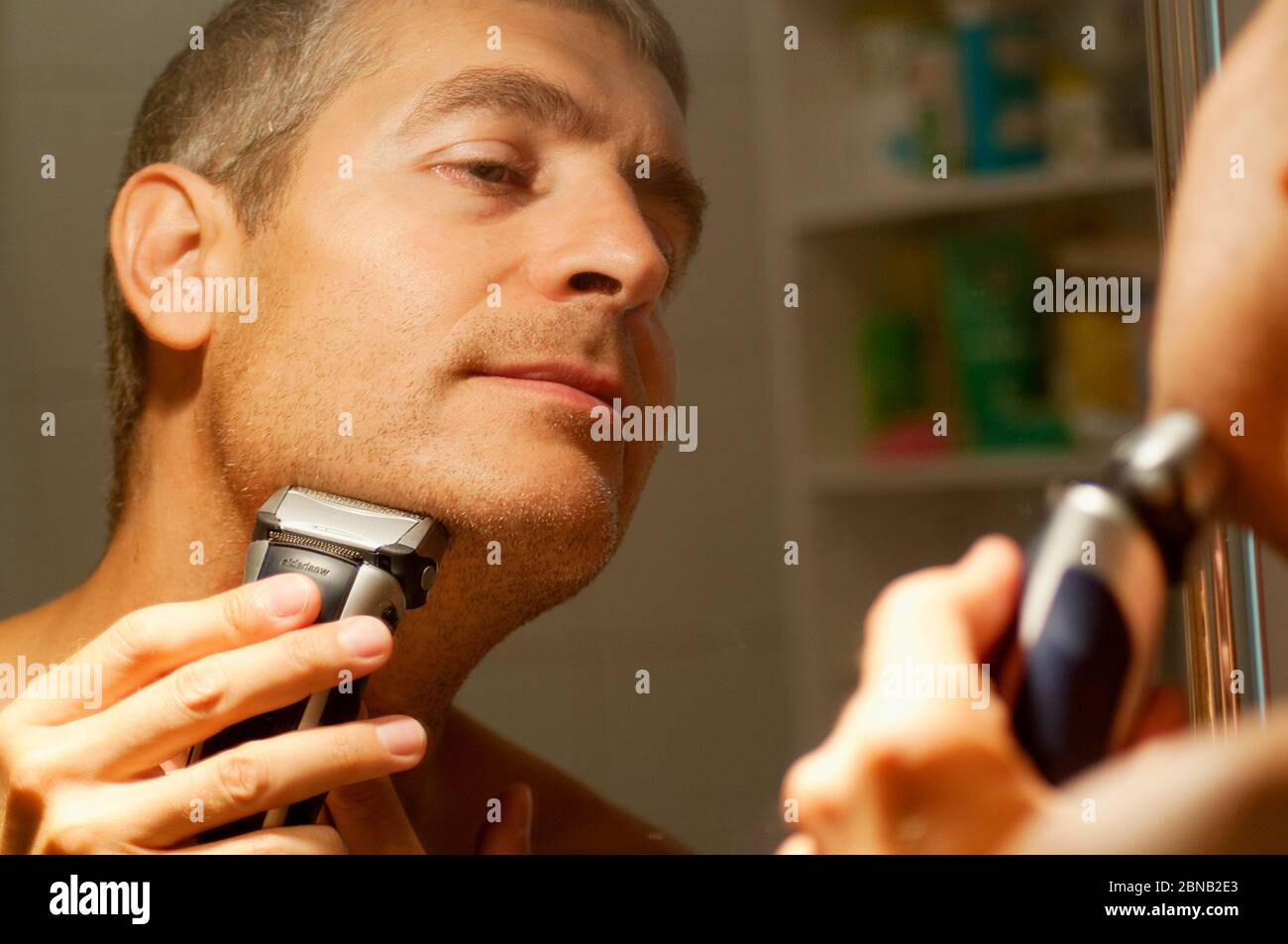 Mature man shaving his beard in front of mirror. Close view. Stock Photo