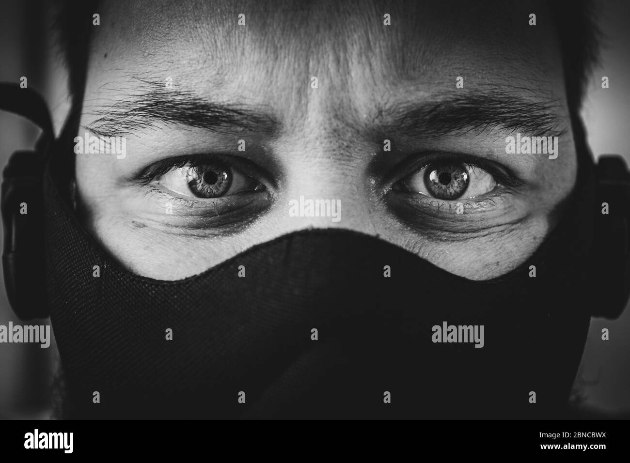 A Greyscale Shallow Shot Of A Male S Face Wearing A Mask Staring Directly Into The Camera Stock Photo Alamy