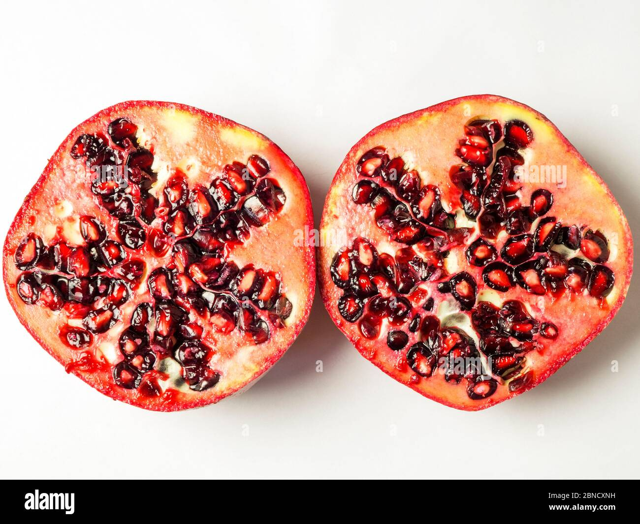 Fresh pomegranate cut in half isolated on a white background Stock Photo