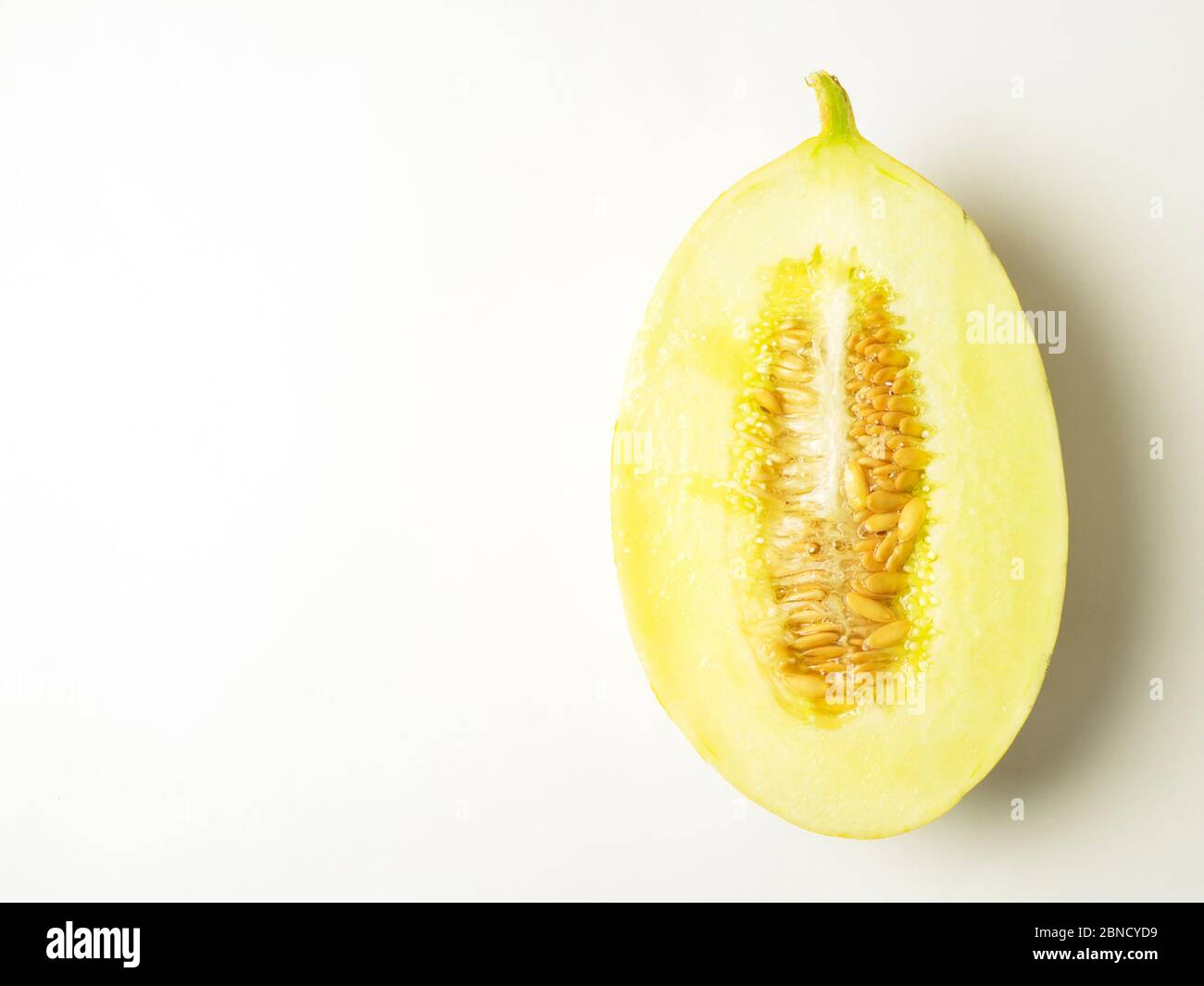 Half a canary melon with seeds on a white background with copy space Stock Photo