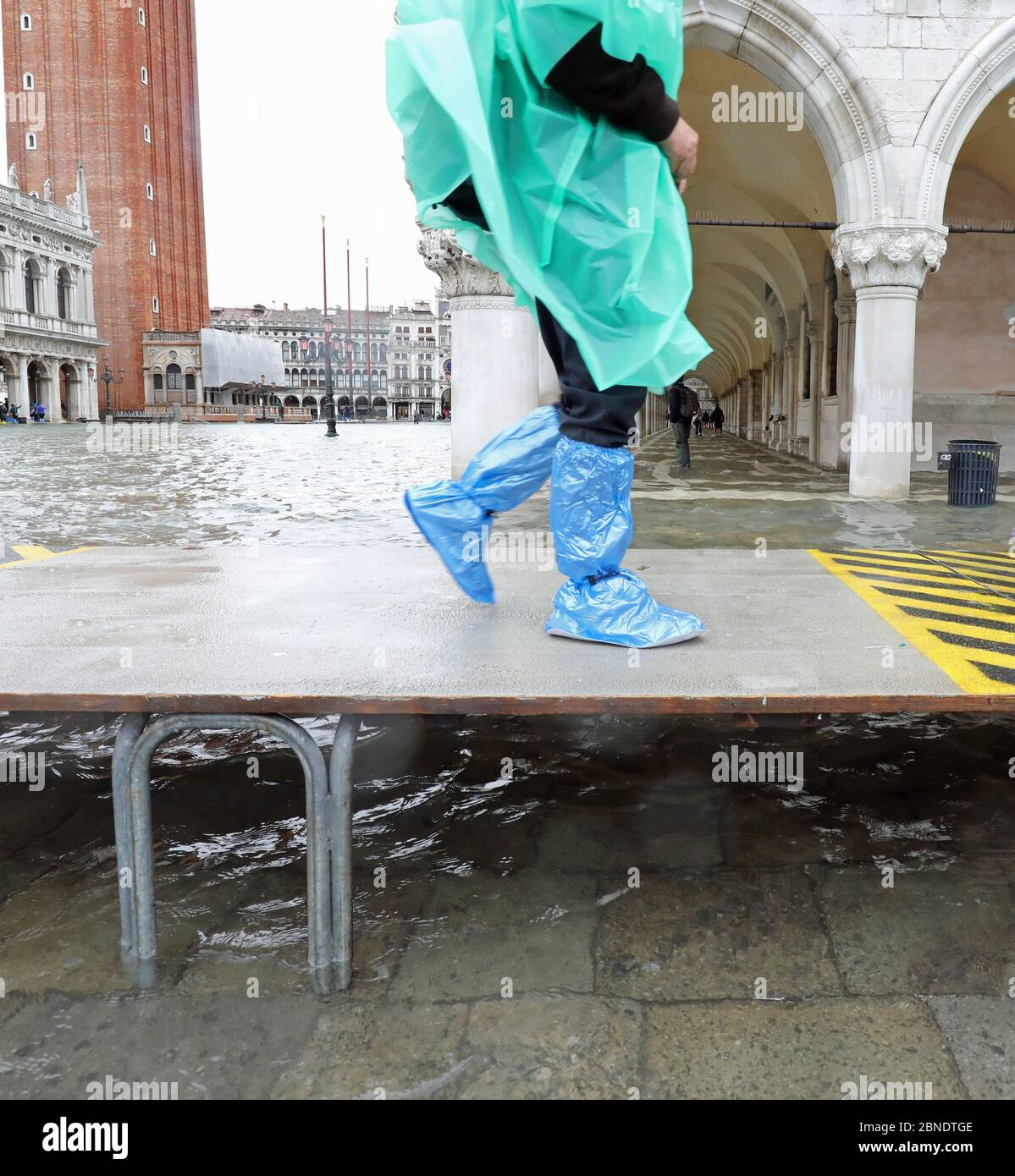 hasty tourist walks fast on the elevated walkway during high tide in Venice in Italy Stock Photo