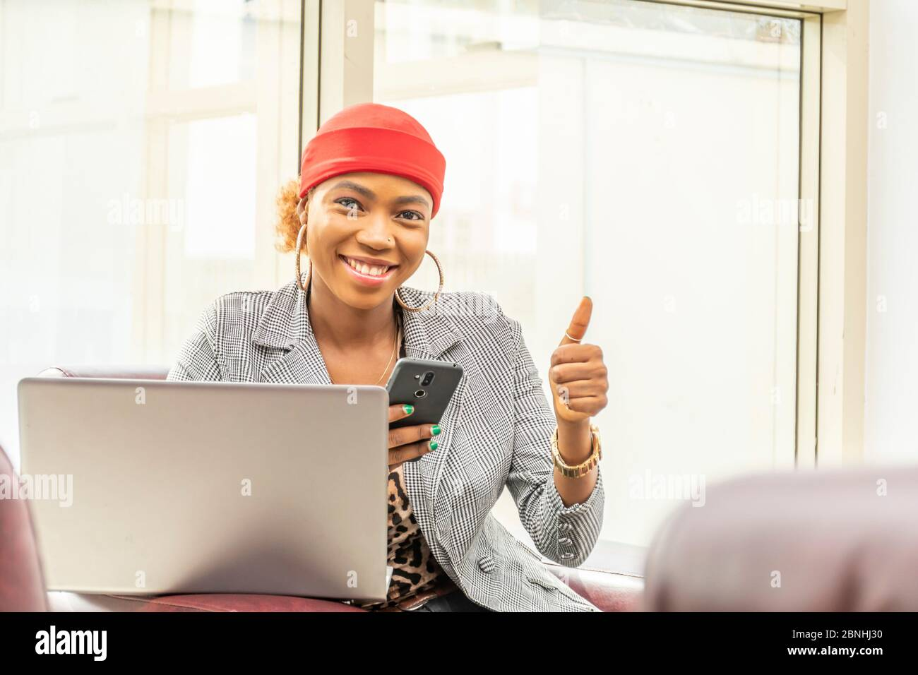 beautiful young african muslim business woman using her laptop computer and smartphone smiling and giving a thumbs up Stock Photo