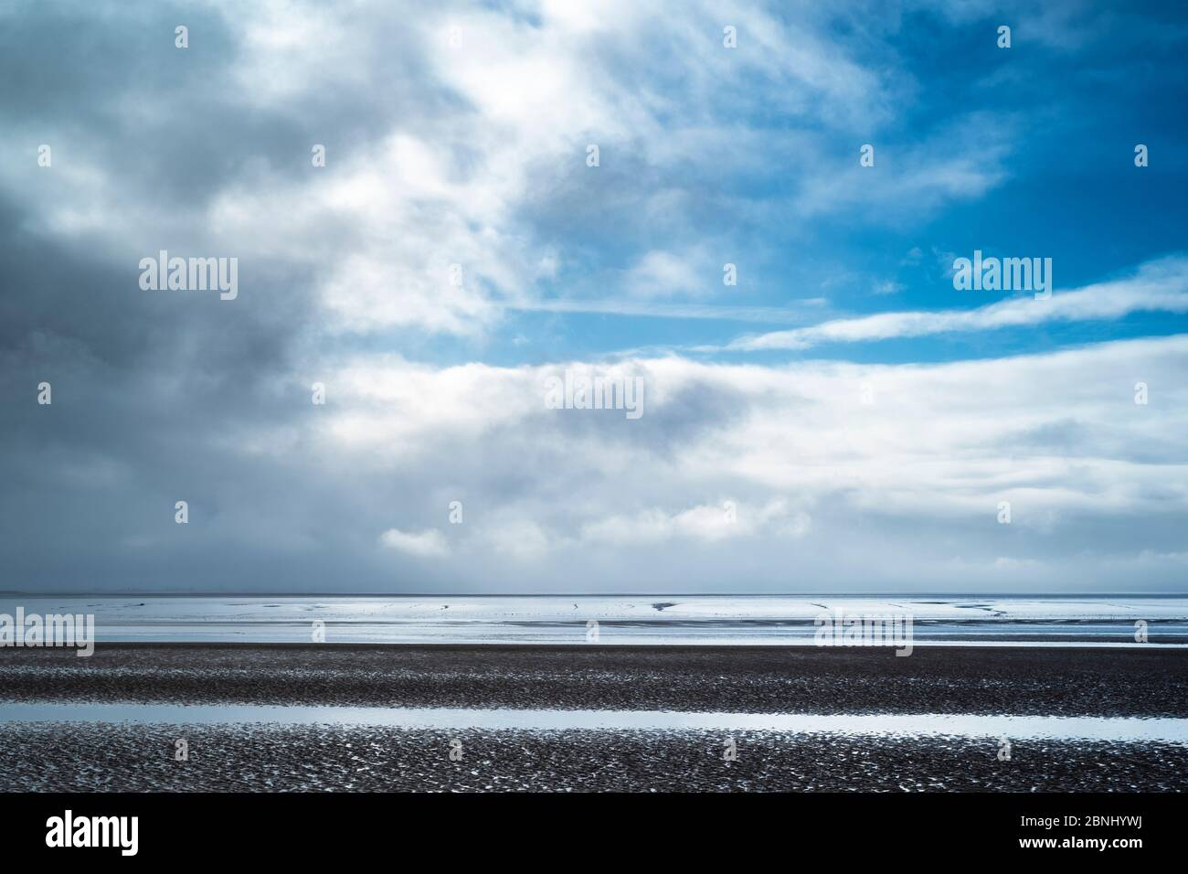 Pastel shades of sea and sandy beach under cerulean sky of the Bristol Channel at Burnham-on-Sea sea shore, Somerset, UK Stock Photo