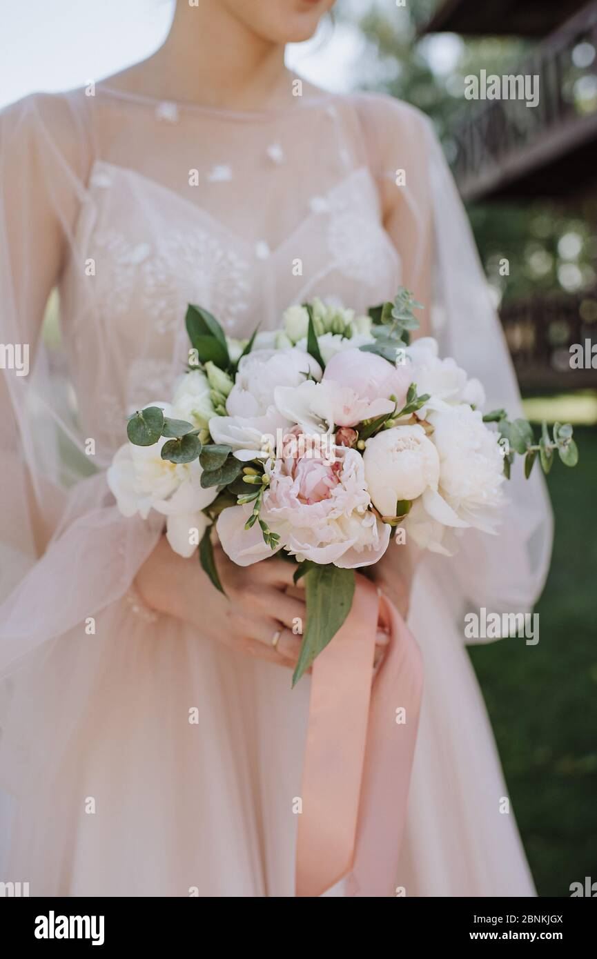 Bride S Bouquet Close Up The Bouquet Consists Of White And Pink Peonies Eucalyptus The Bride Dressed In Pink Wedding Dress Holds The Bouquet Stock Photo Alamy