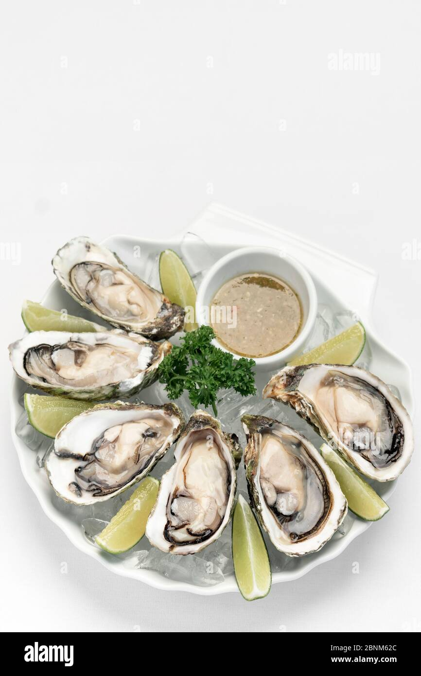 Six fresh oysters with lime wedges and citrus vinaigrette sauce Stock Photo