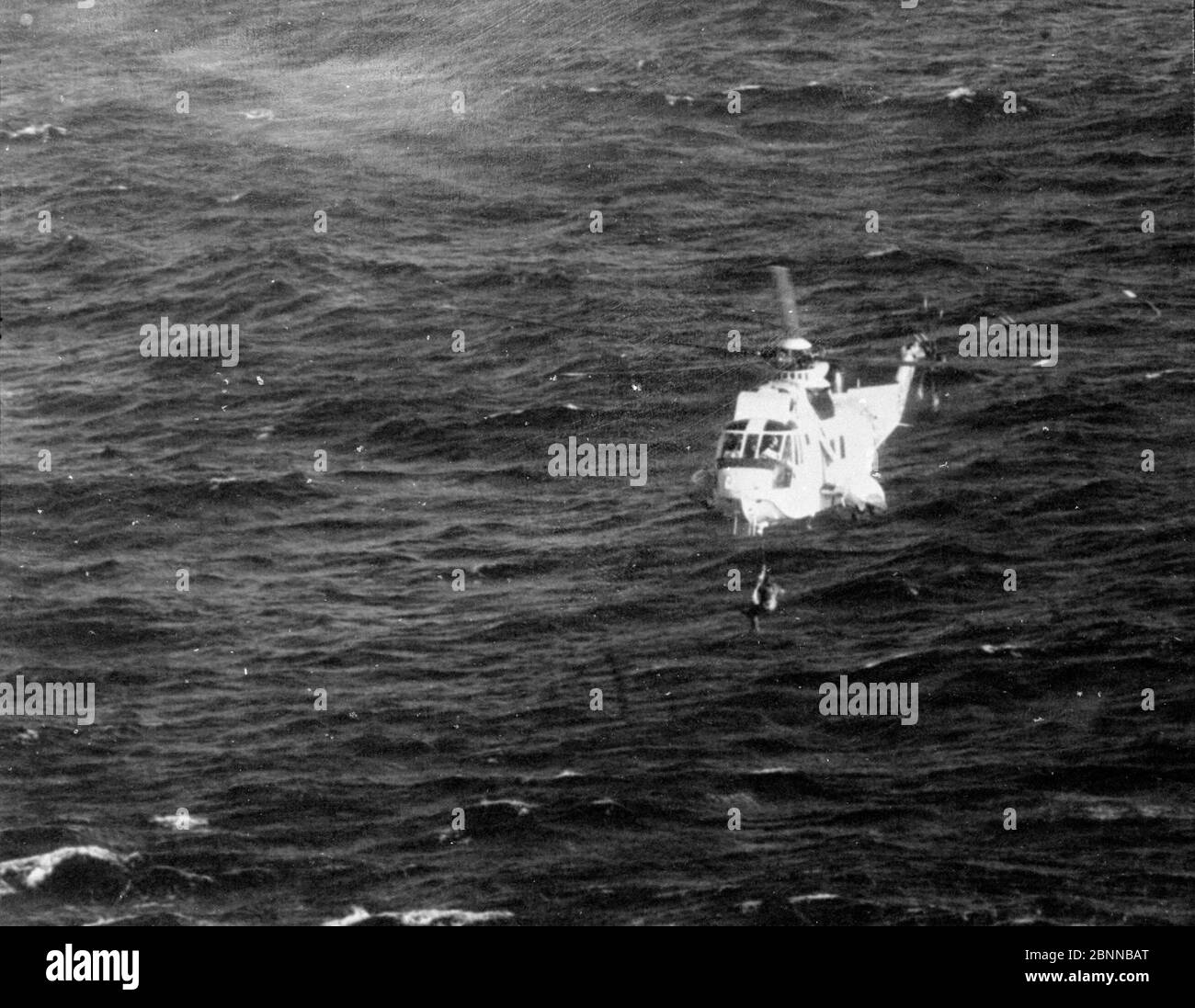 AJAXNETPHOTO. 8TH JUNE, 1980. WESTERN APPROACHES. - FRENCH SOLO YACHTSMAN RESCUE - A ROYAL NAVAL AIR SERVICE SEA KING HELICOPTER HOISTING FRENCH YACHTSMAN JACQUES TIMSIT TO SAFETY FROM THE OCEAN AFTER HIS TRANSATLANTIC RACE YACHT MOTOROLA 38 HIT A SUBMERGED OBJECT AND SANK FOUR DAYS INTO THE SINGLE HANDED RACE FROM PLYMOUTH UK TO NEWPORT, RHODE ISLAND.PHOTO:AJAX NEWS PHOTOS/AJAX NEWS & FEATURE SERVICE REF:8011061 1 086 Stock Photo