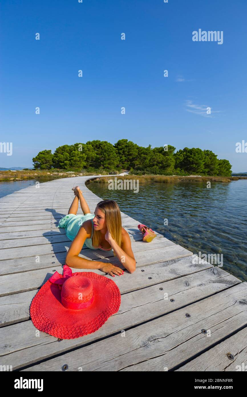 Summer teengirl lying on stomach alone lonesome on wooden quay boring looking away aside morning sun Stock Photo