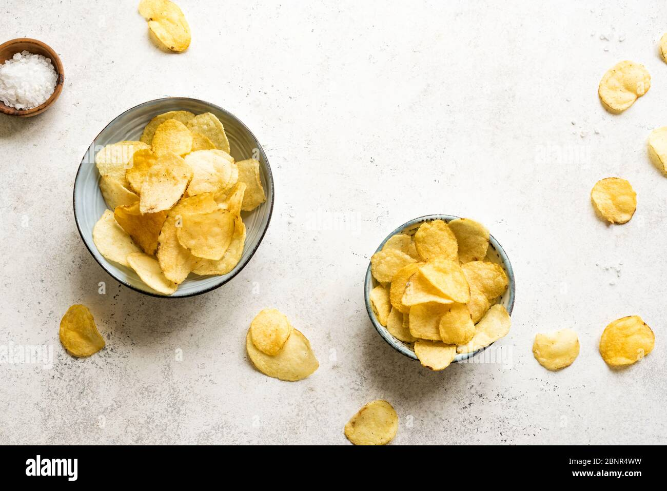 Homemade potato chips in bowls. Crispy potato chips on white background, top view, copy space. Stock Photo