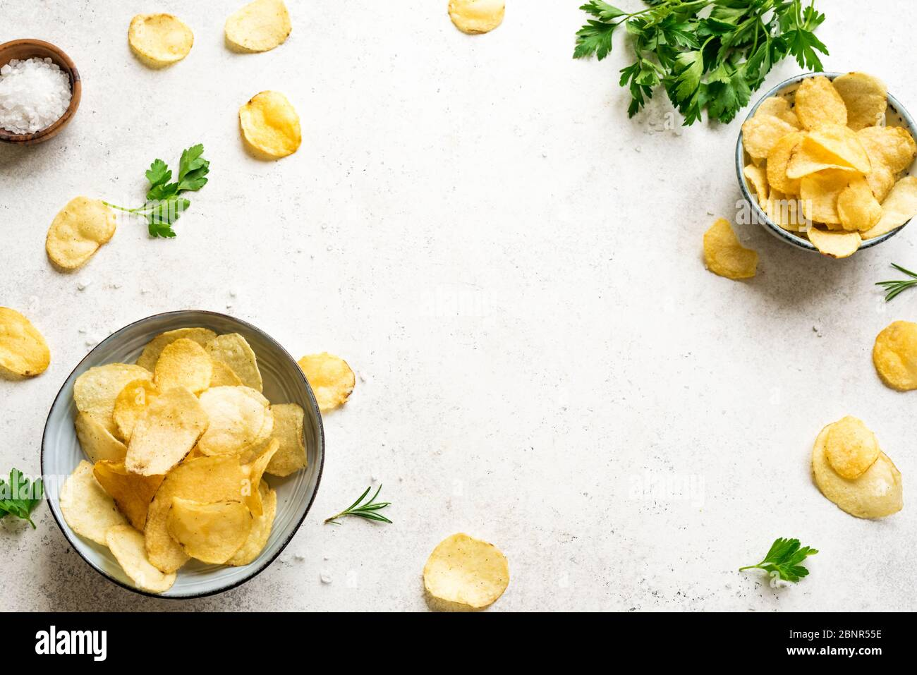 Potato chips in bowls. Homemade oven baked crispy potato chips on white background, top view, copy space. Stock Photo