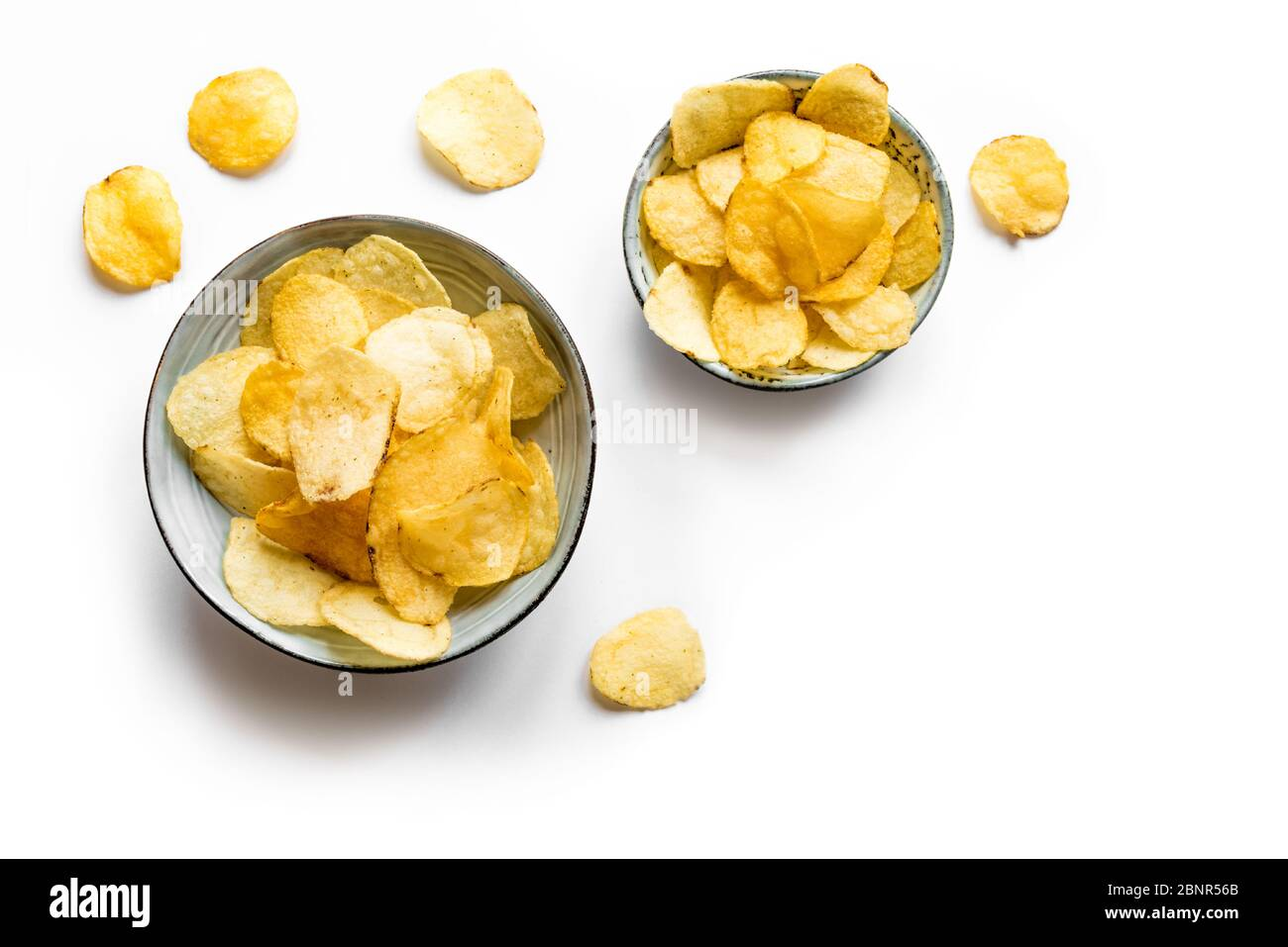 Potato chips in bowls isolated on white background. Homemade oven baked crispy potato chips, top view, copy space. Stock Photo