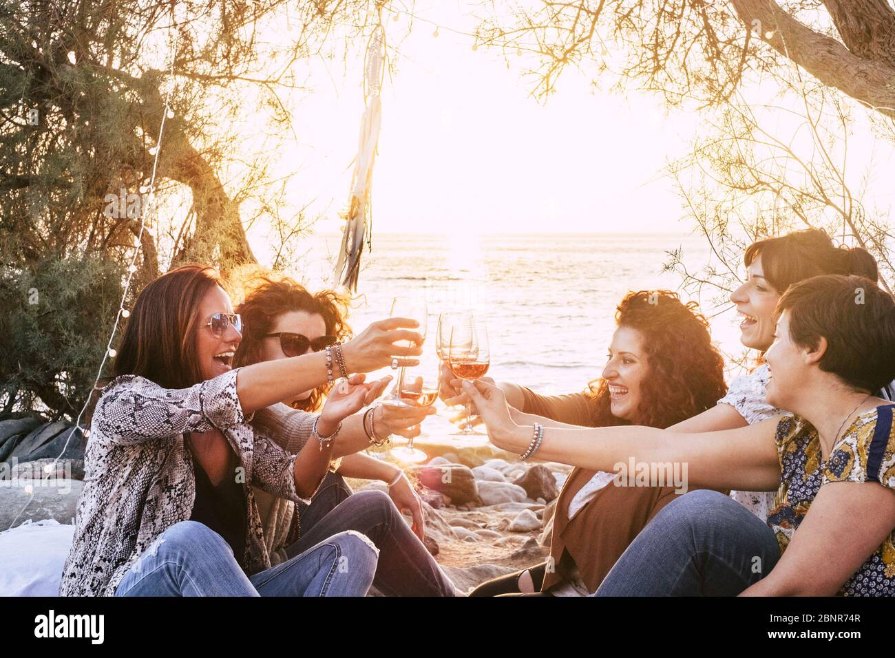 Group of middle age young adult women having fun together toasting and clinking with wine glasses at the beach during a golden sunset enjoying outdoor leisure activity or vacation Stock Photo