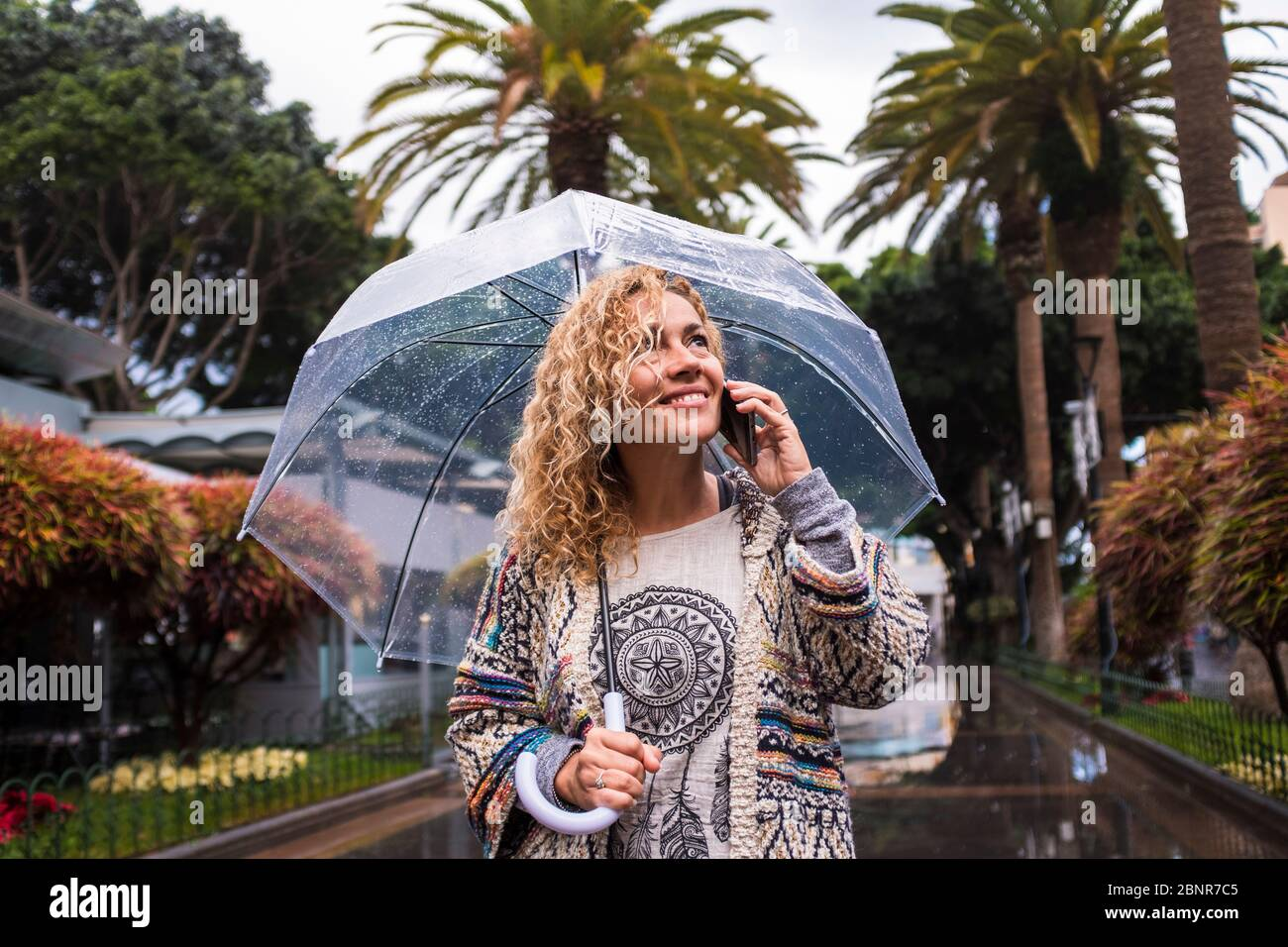 Attractive and cheerful fashion trendy middle age young caucasian woman walking in the city under the rain with a transparent umbrella - cold season concept enjoying the urban park Stock Photo