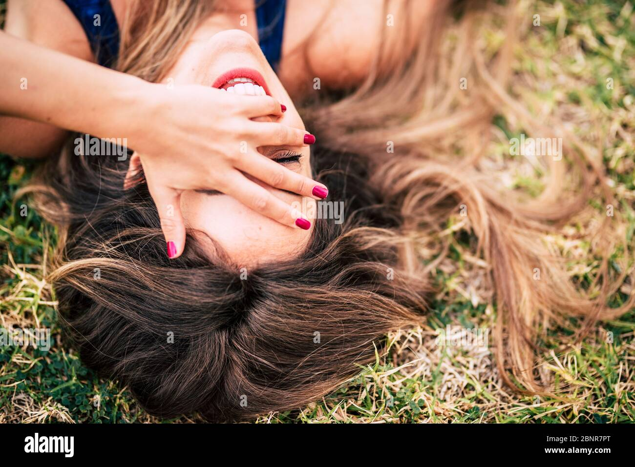 Laugh and cheerful people young caucasian woman lay down on the grass and laughing a lot with hand on face - beautiful healthy long brown hair and happiness joyful concept Stock Photo