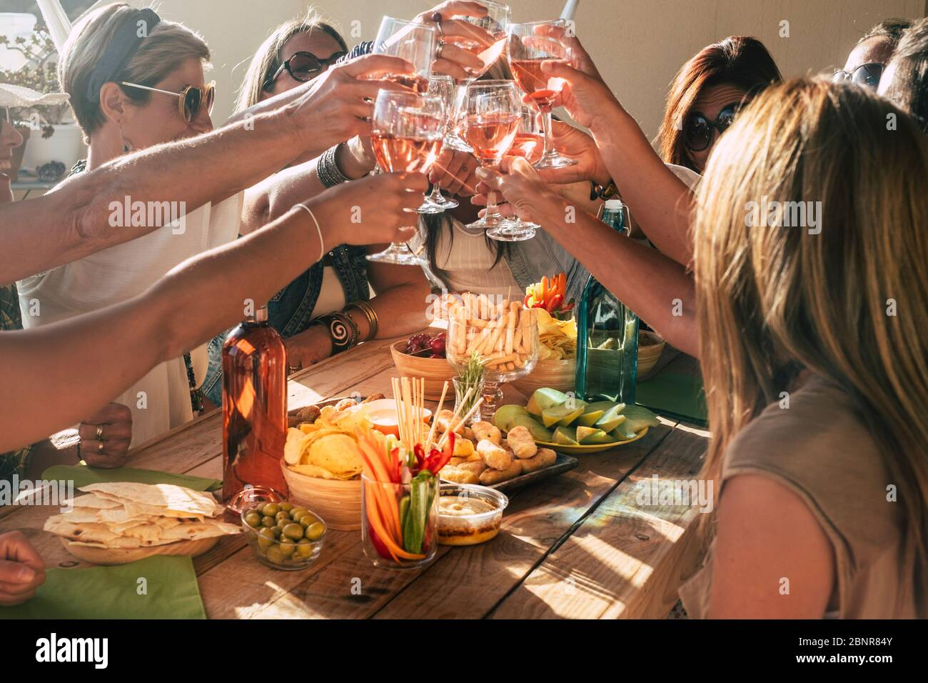 Group of happy and cheerful caucasian people women have fun all together drinking and toasting with red wine - friendship and holiday celebration concept with adult females Stock Photo