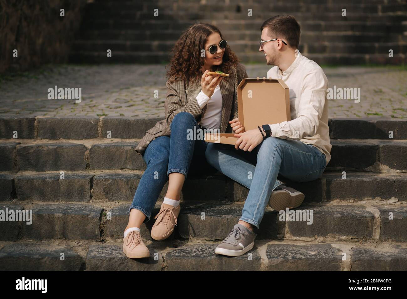 Young couple sitting on stairs outdoor and eating pizza. Handsome man with beaufitul woman taste pizza with vegetables. Vegan fast food Stock Photo
