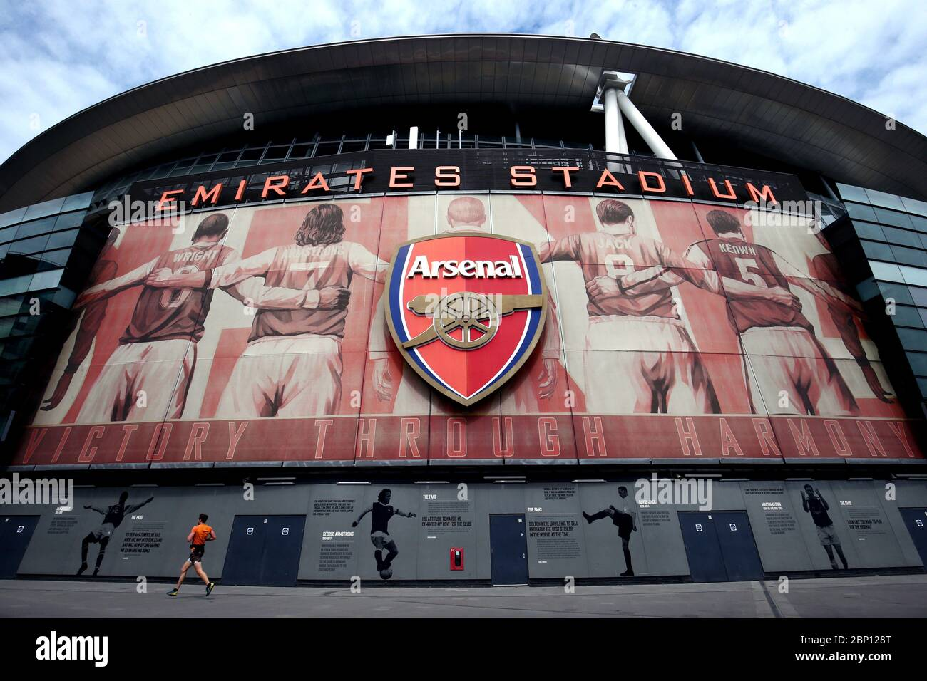 A lone jogger runs past the Emirates Stadium, home of Arsenal, today should have seen Arsenal take on Watford in what would have been their final Premier League game of the 19/20 season. Stock Photo