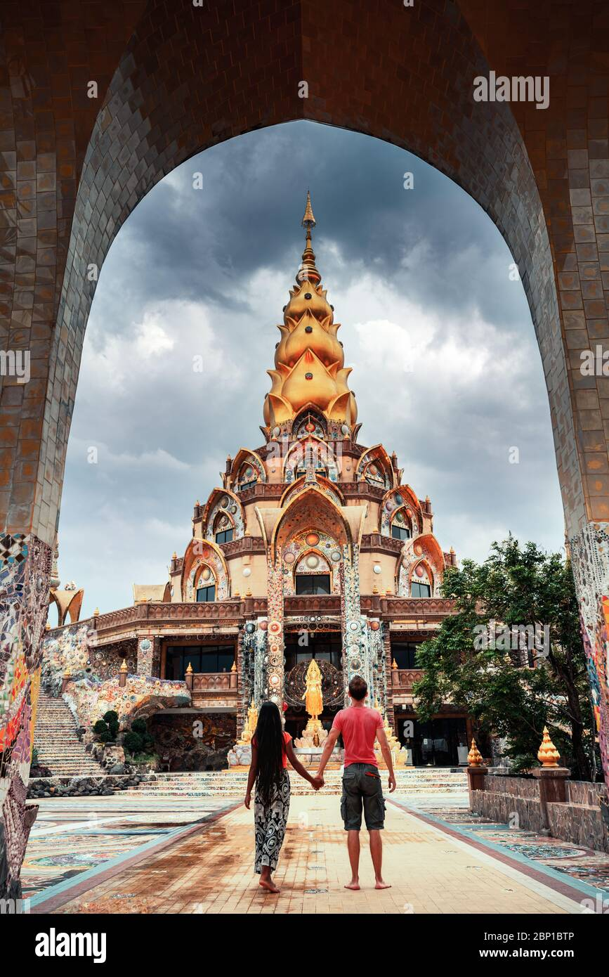Happy travel couple explore scenery Thai architecture in the Lanna style in buddhist Thailand temple. Asian culture and religion Stock Photo
