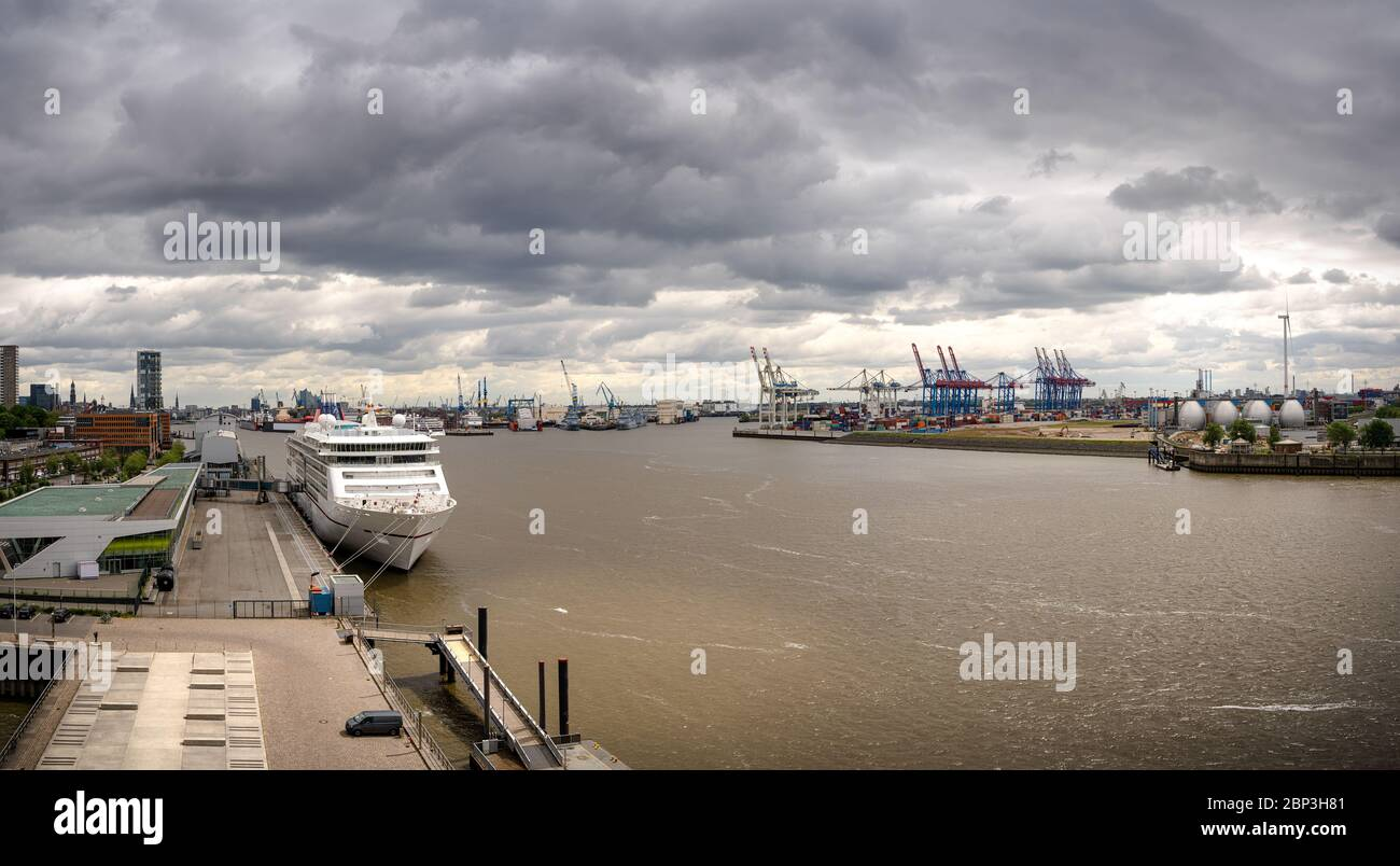 Panorama of a container terminal and industrial facilities in the port of Hamburg with a cruise liner Stock Photo